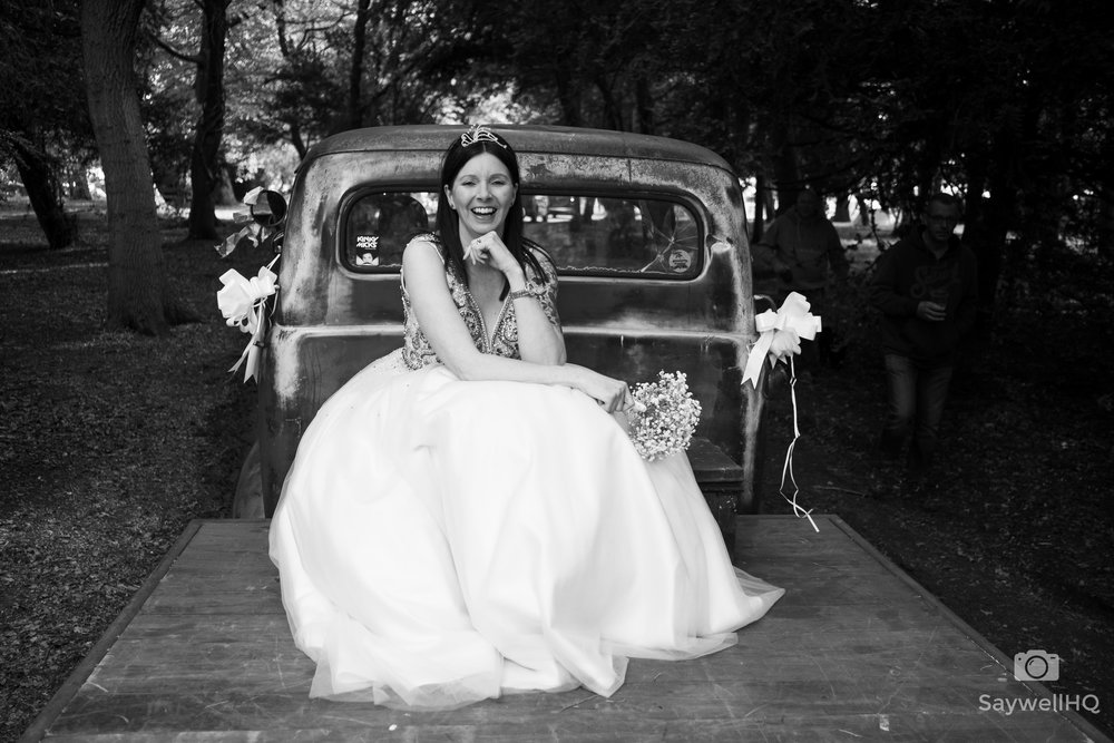 fun wedding image of a bride on the back of a truck