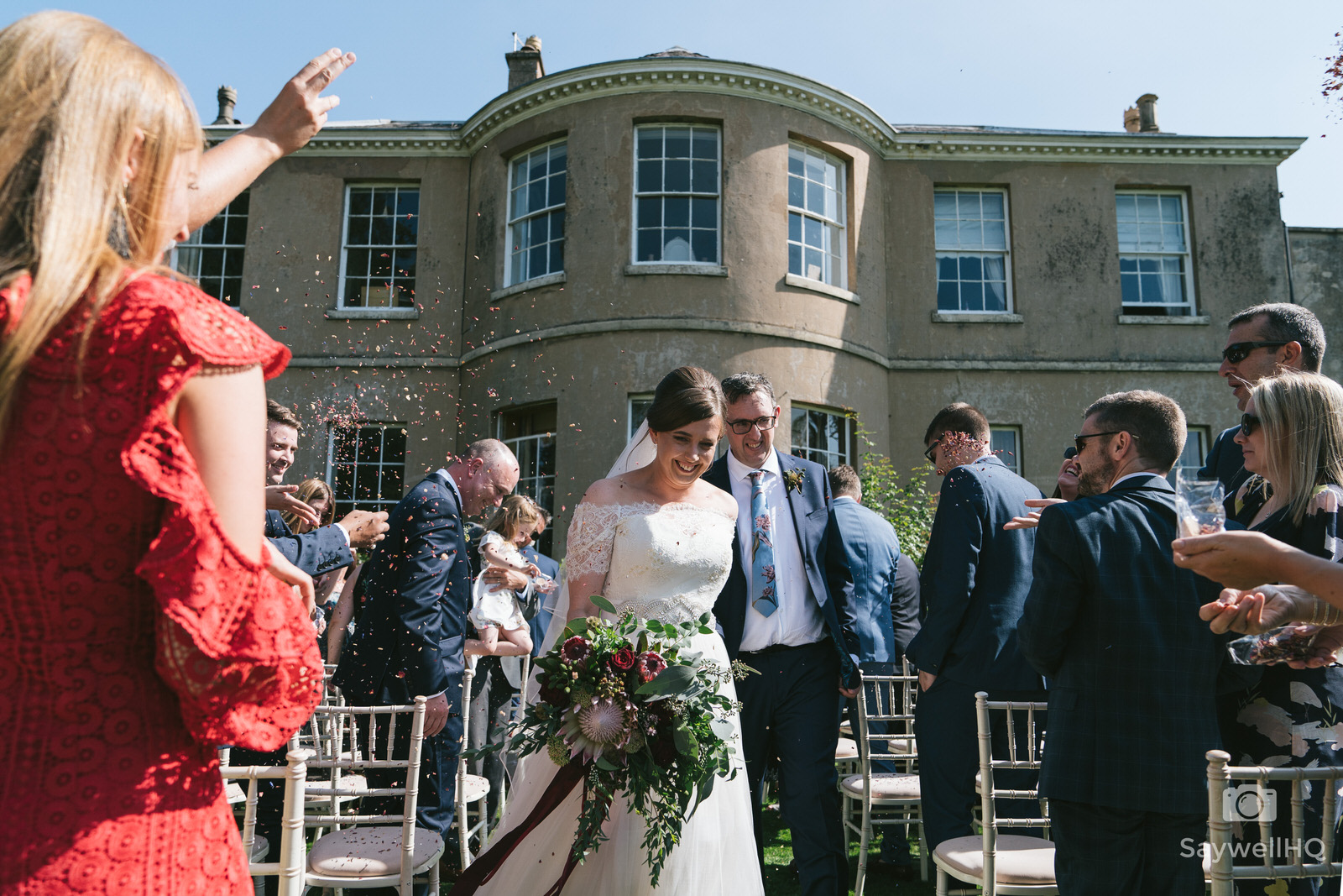 Wedding photographer Nottingham - bride and groom walking through the confetti at East Bridgford Hill wedding venue