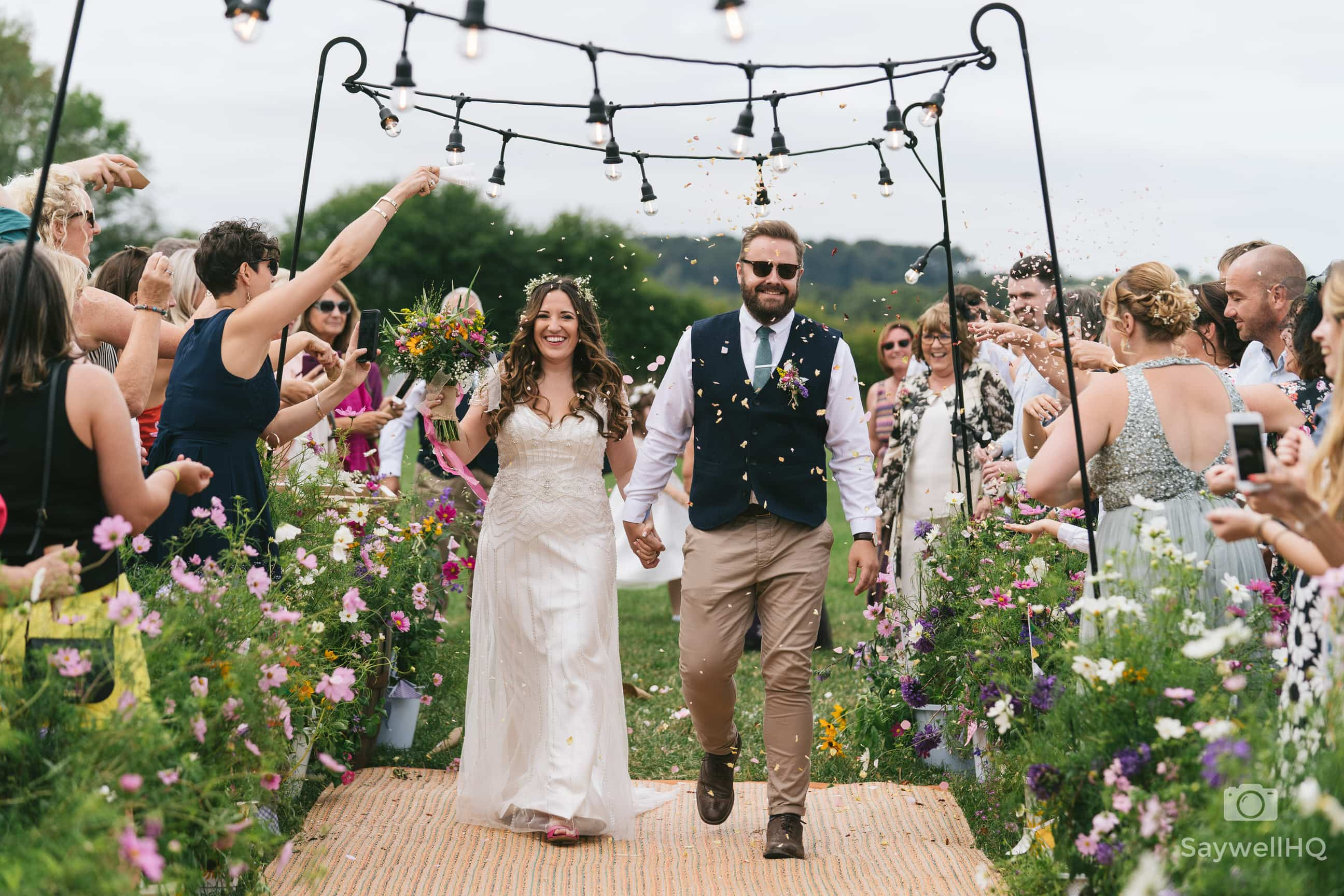 Wedding Photography at Mapperley Farm - bride and groom walking through confetti being thrown at them by the wedding guests