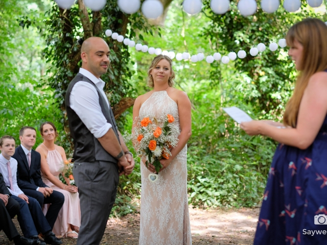 Humanist wedding photography - bride and groom looking at a lady in a blue dress giving a reading