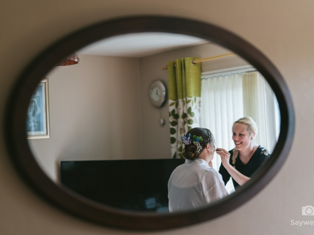 Swancar Farm Wedding Photography brides hair being done in the reflection of a mirror