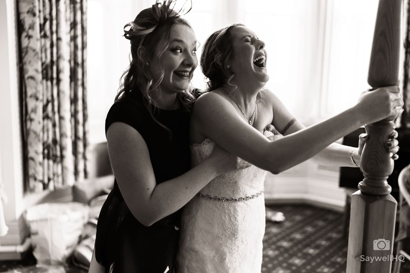 Bestwood Lodge wedding photography Bride and bridesmaid having fun getting in to the wedding dress at a wedding at the bestwood lodge hotel