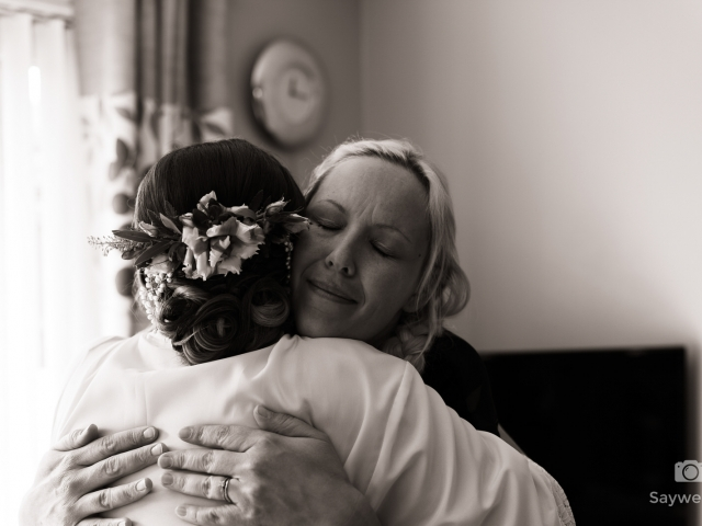 Swancar Farm Wedding Photography bride  and makeup artist hugging in a living room