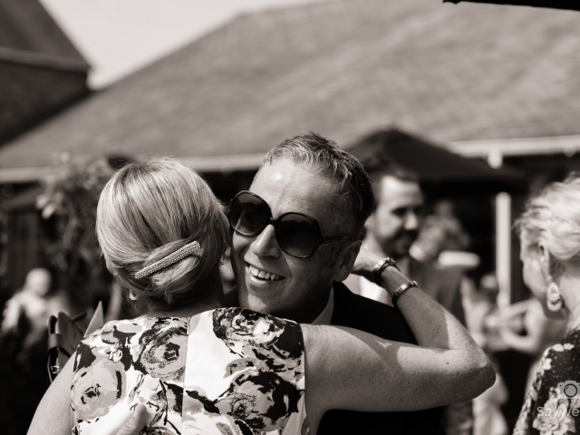 Swancar Farm Wedding Photography guests hug in strong sunlight