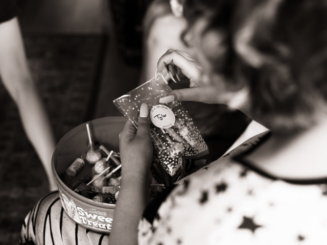 Swancar Farm Wedding Photography bridesmaid putting sweets in a bag for wedding favours