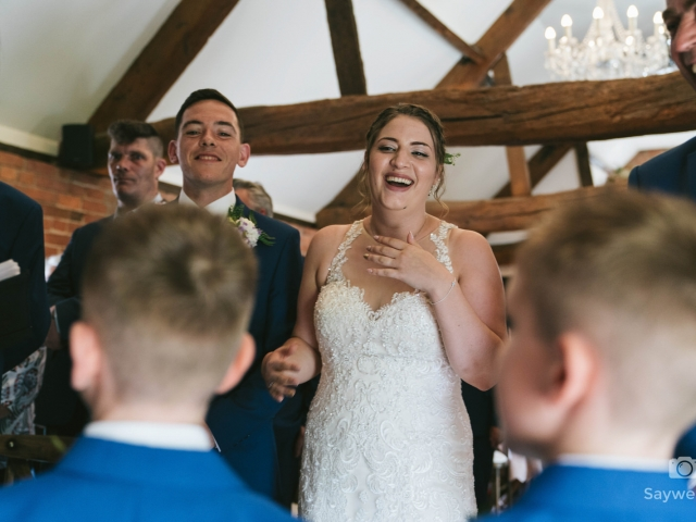Swancar Farm Wedding Photography bride laughing out loud at the page boys