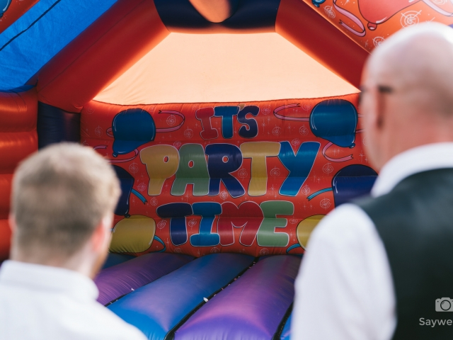 Swancar Farm Wedding Photography guests looking at the bouncy castle which says its party time