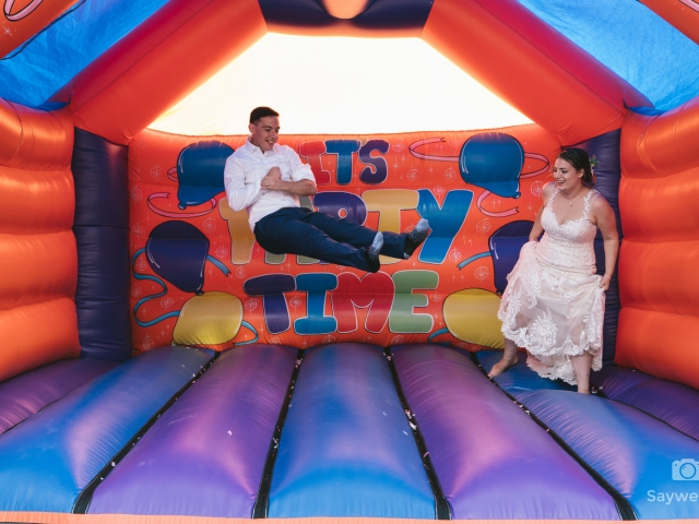 Swancar Farm Wedding Photography bride and groom on the bouncy castle groom is in mid air