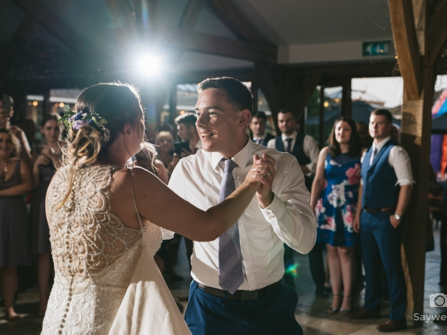 Swancar Farm Wedding Photography bride and groom dance with each other with the guests looking on