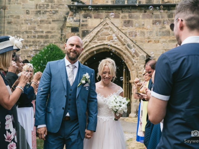 Elvaston Castle Wedding Photography + bride + groom leaving the wedding after a church service with bubbles for confetti