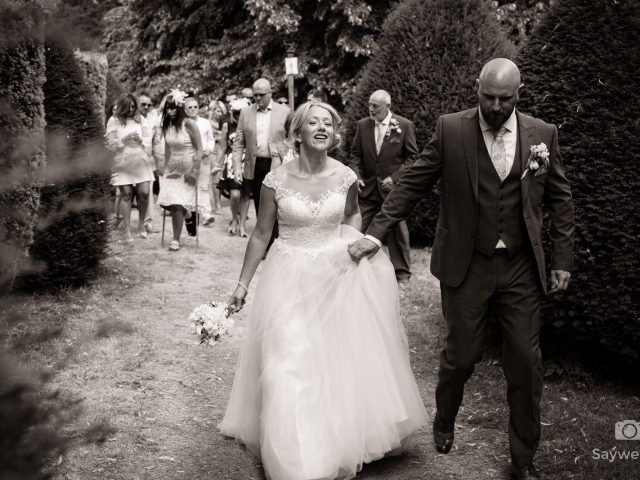Elvaston Castle Wedding Photography + bride + groom walking away from the church + groom holding brides dress