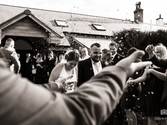 Wedding photography at Goosedale - bride and groom running through the confetti being thrown by their wedding guests