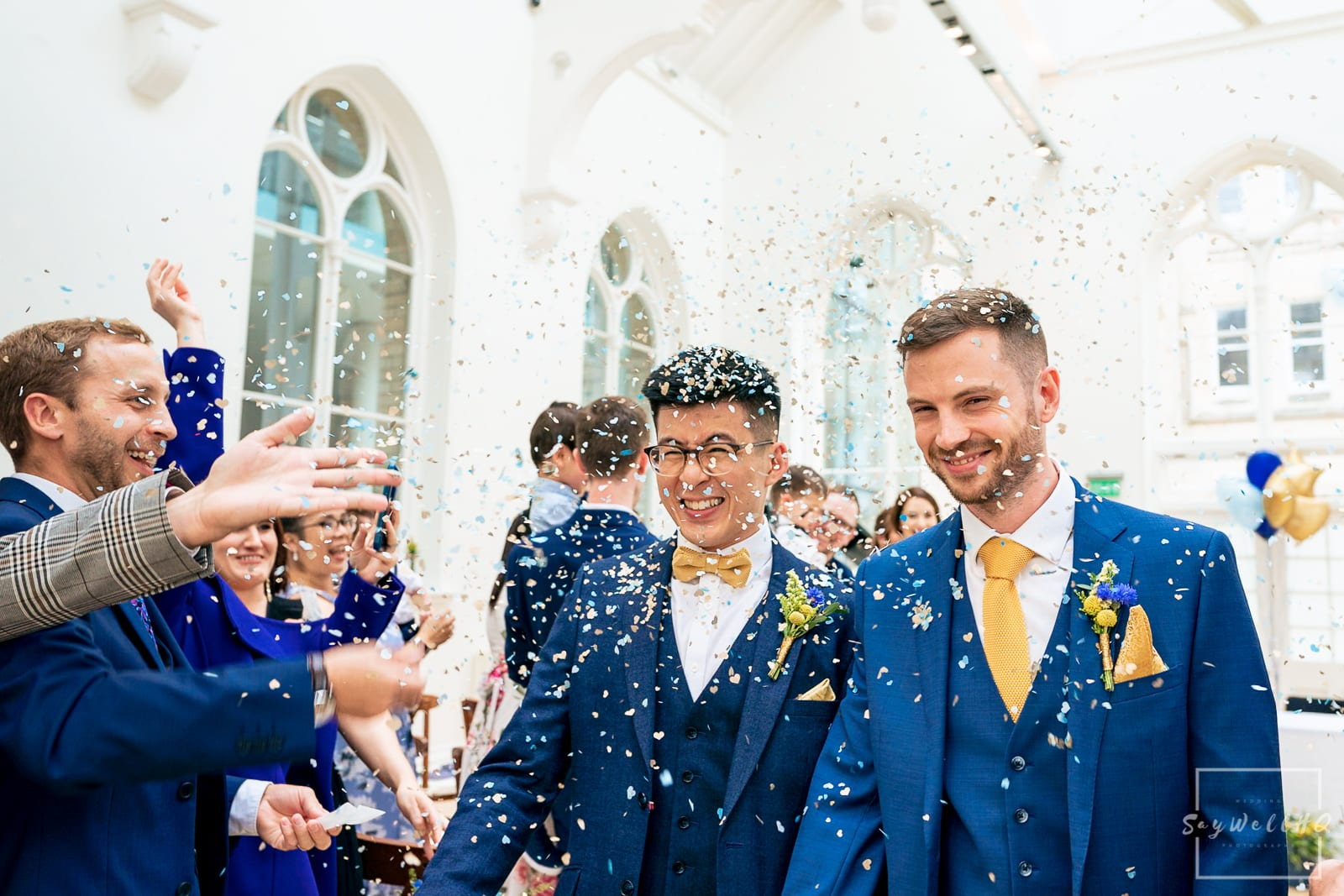 Nottingham Same sex wedding photographer - happy couple walking through the wedding confetti at a Nottingham wedding