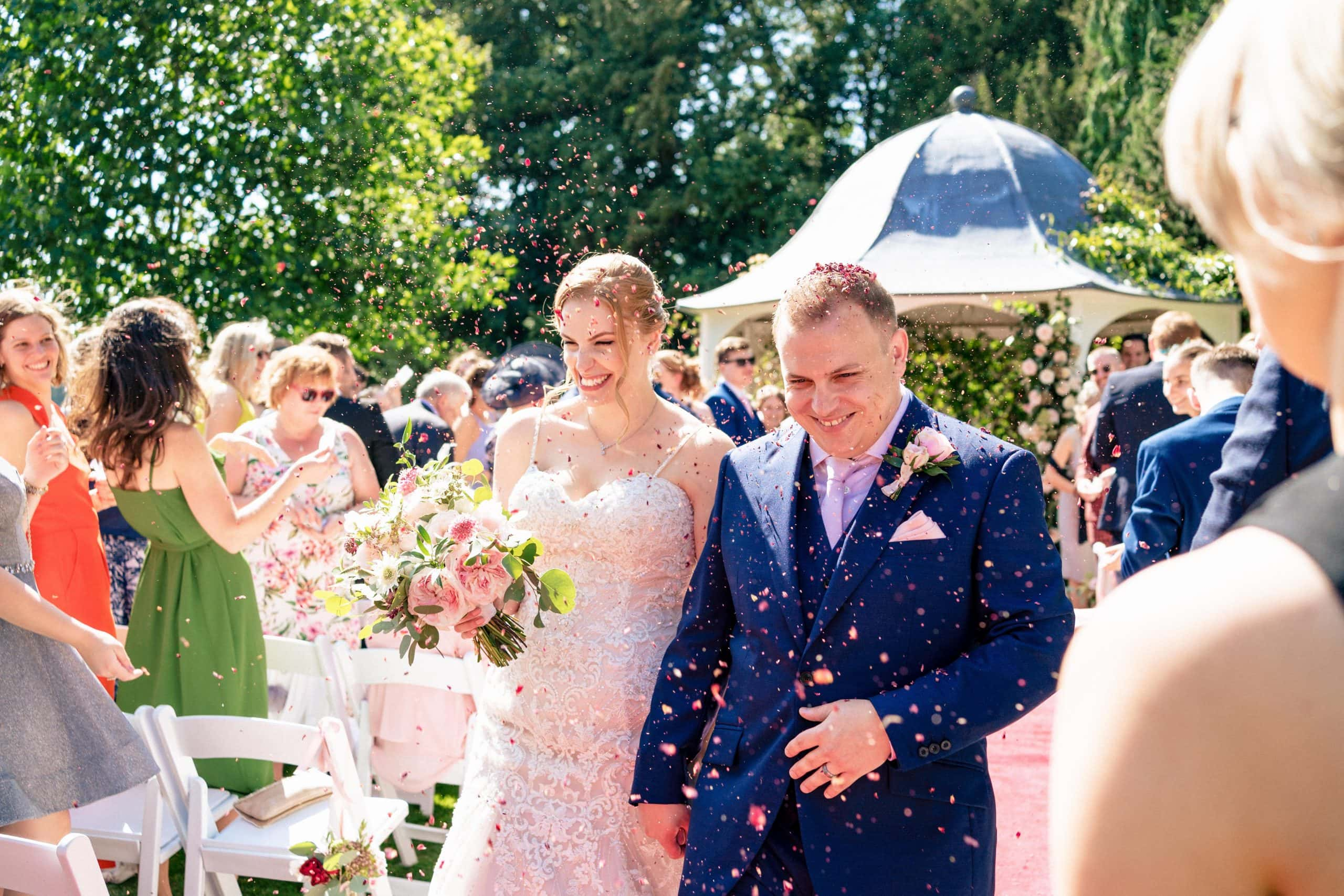 Wedding photography at Prestwold Hall - bride and groom confetti outside in the grounds of prestwold hall