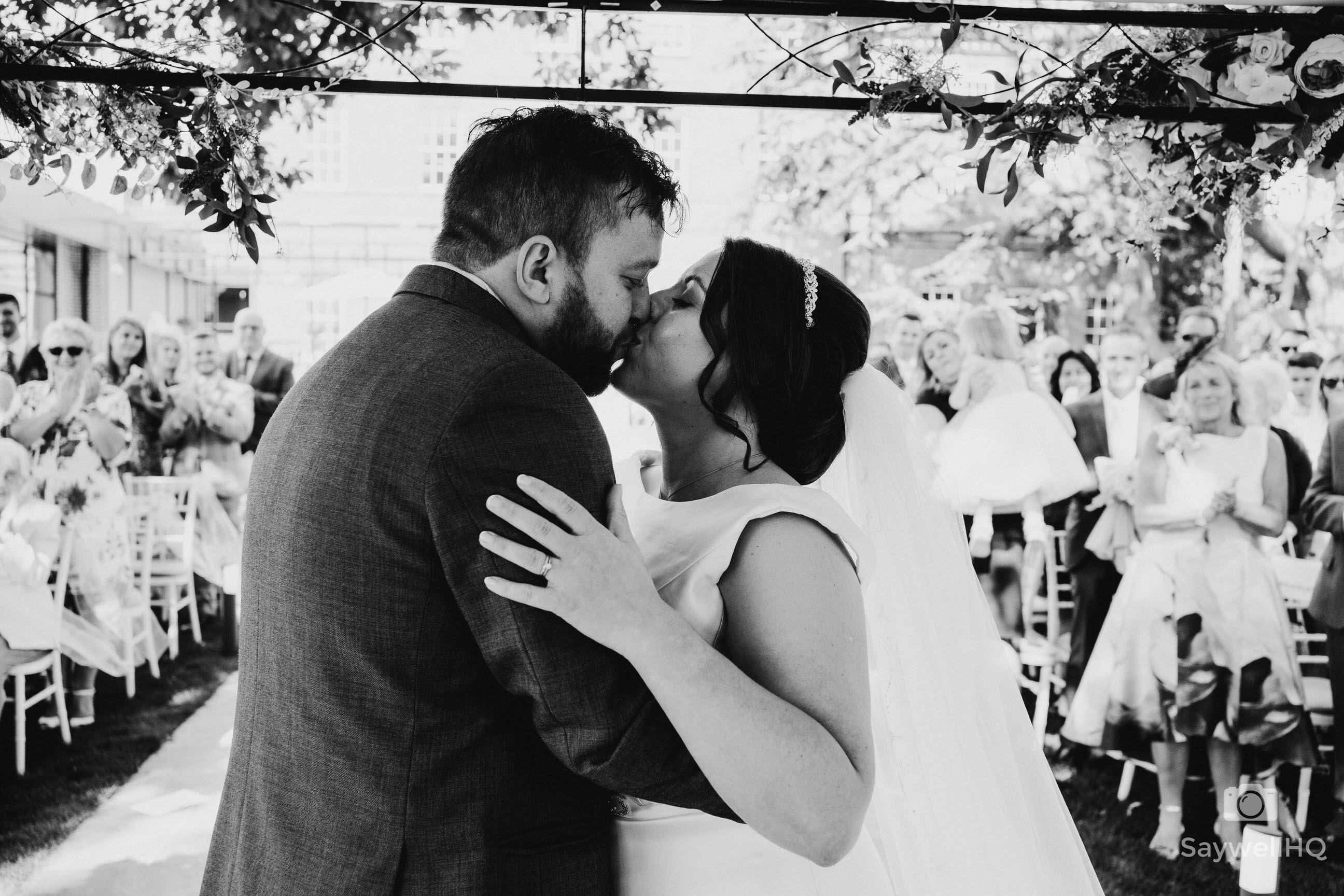 Leicester Wedding Photography at Winstanley House - bride and groom first kiss in outdoor wedding ceremony