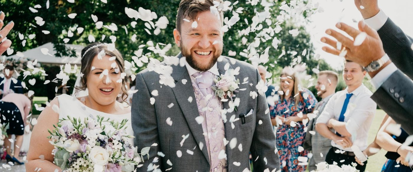 Winstanley House Wedding - Bride and groom walk through the confetti after an outdoor ceremony