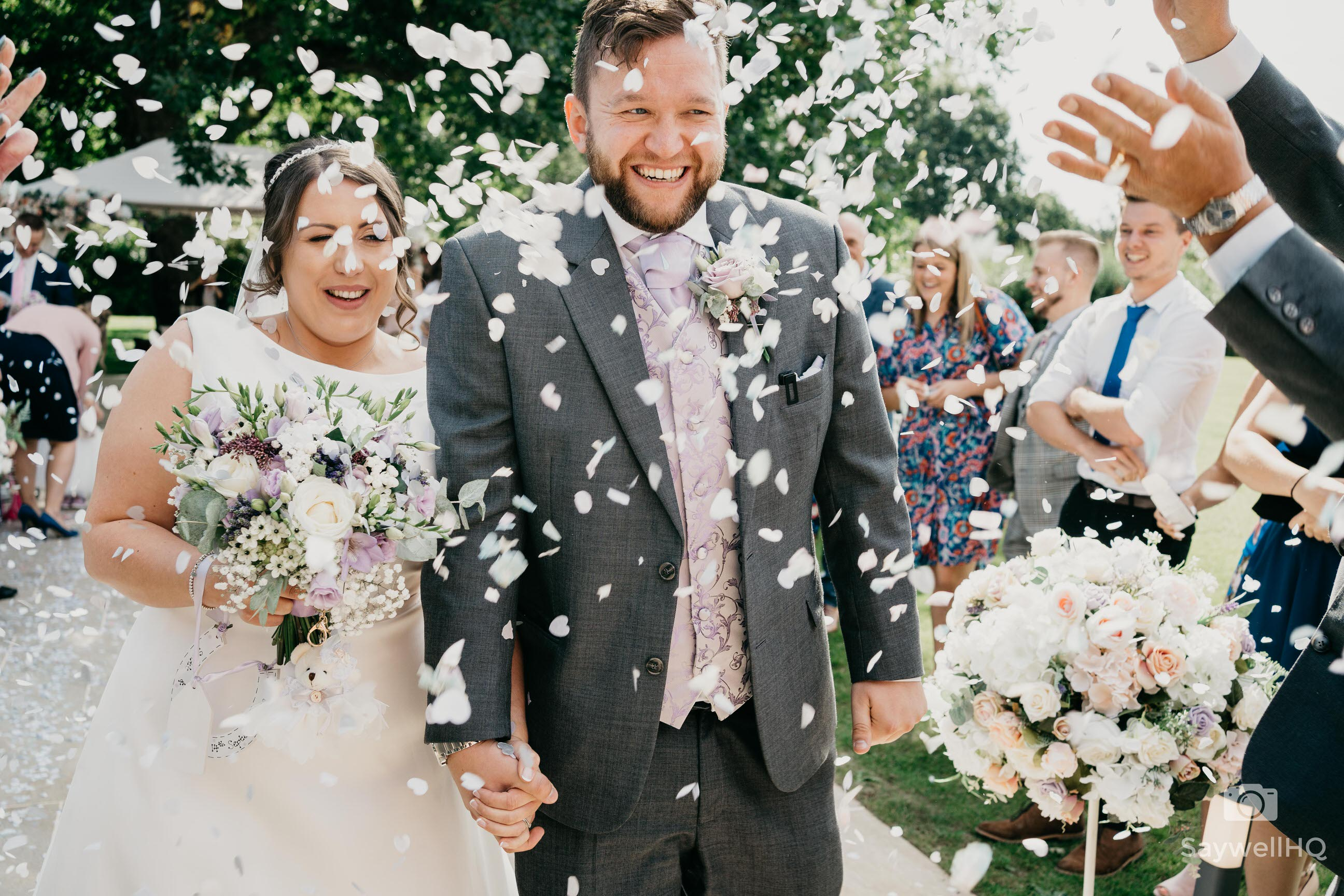 Wedding photography reviews - bride and groom walking through confetti at their wedding at Winstanley House