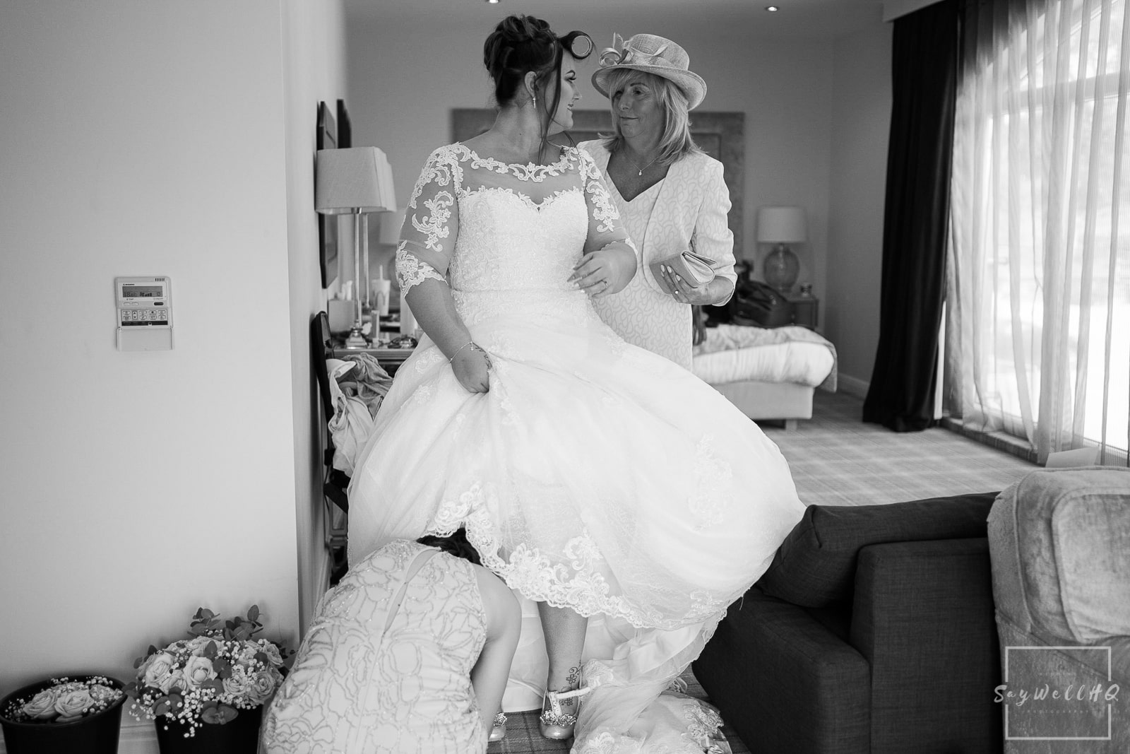 PEAK EDGE HOTEL WEDDING PHOTOGRAPHY - bride puts on her wedding dress with help from her mother and bridesmaids