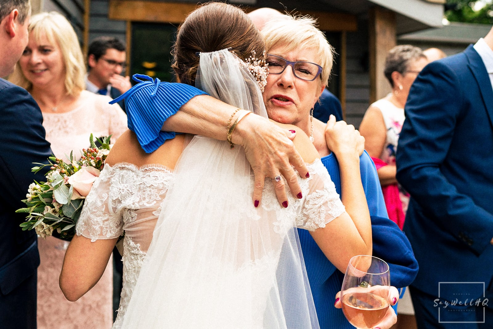 The Chequers Inn Woolsthorpe Wedding Photography - bride hugs with guests in the pub garden