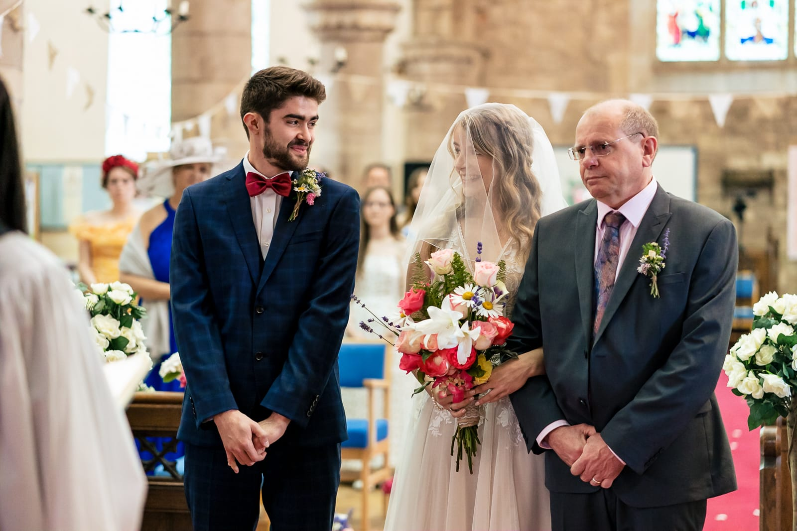 bride and groom looking lovingly at each other during their wedding ceremony at the St Peters Church in Bromyard Herefordshire.