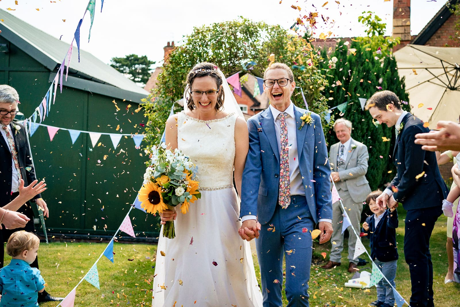 bride and groom get covered in confetti in the grounds of the Church in Melbourne in Derbyshire