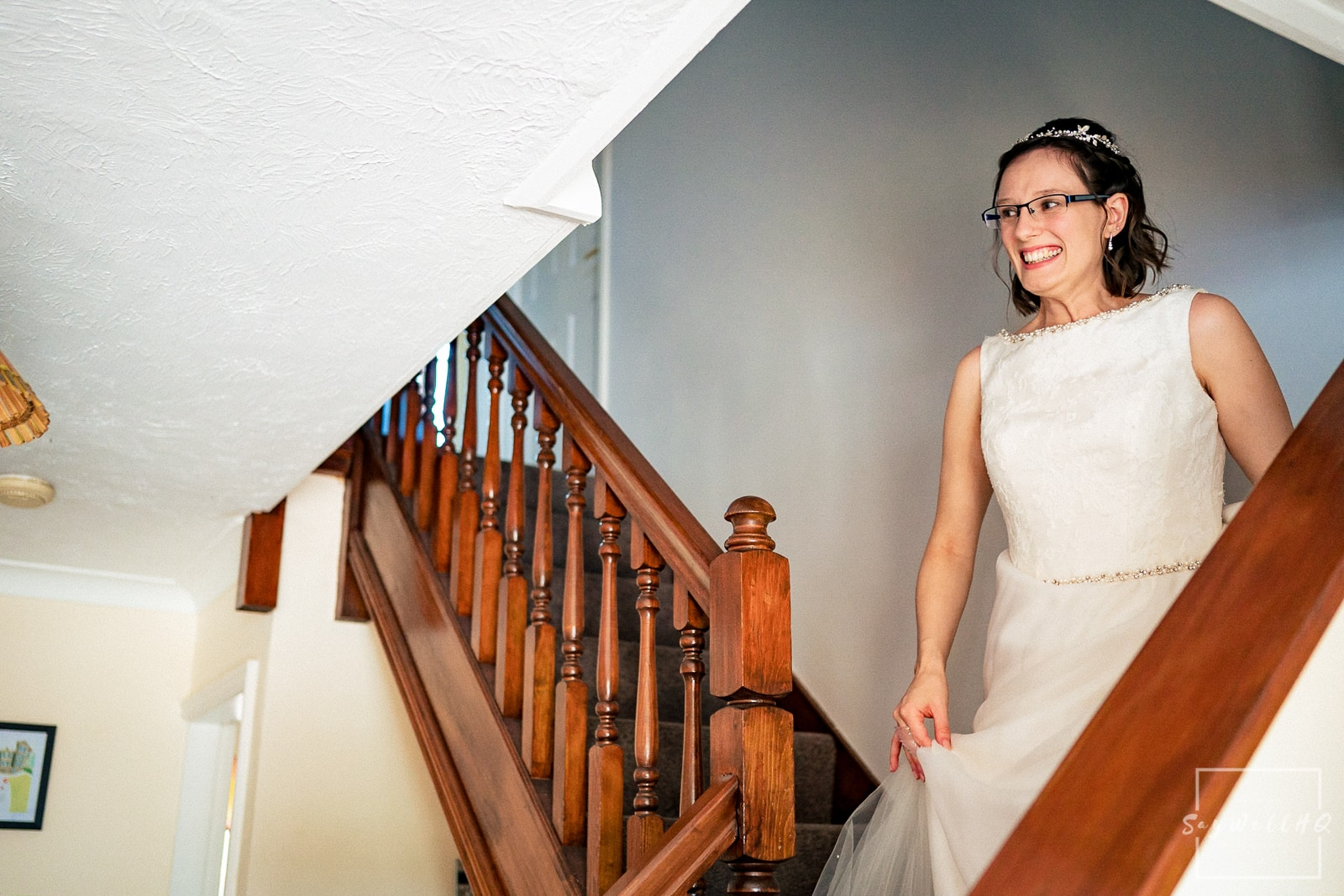 bride excited to show here family and friends her wedding dress when walking down the stairs at her parents home
