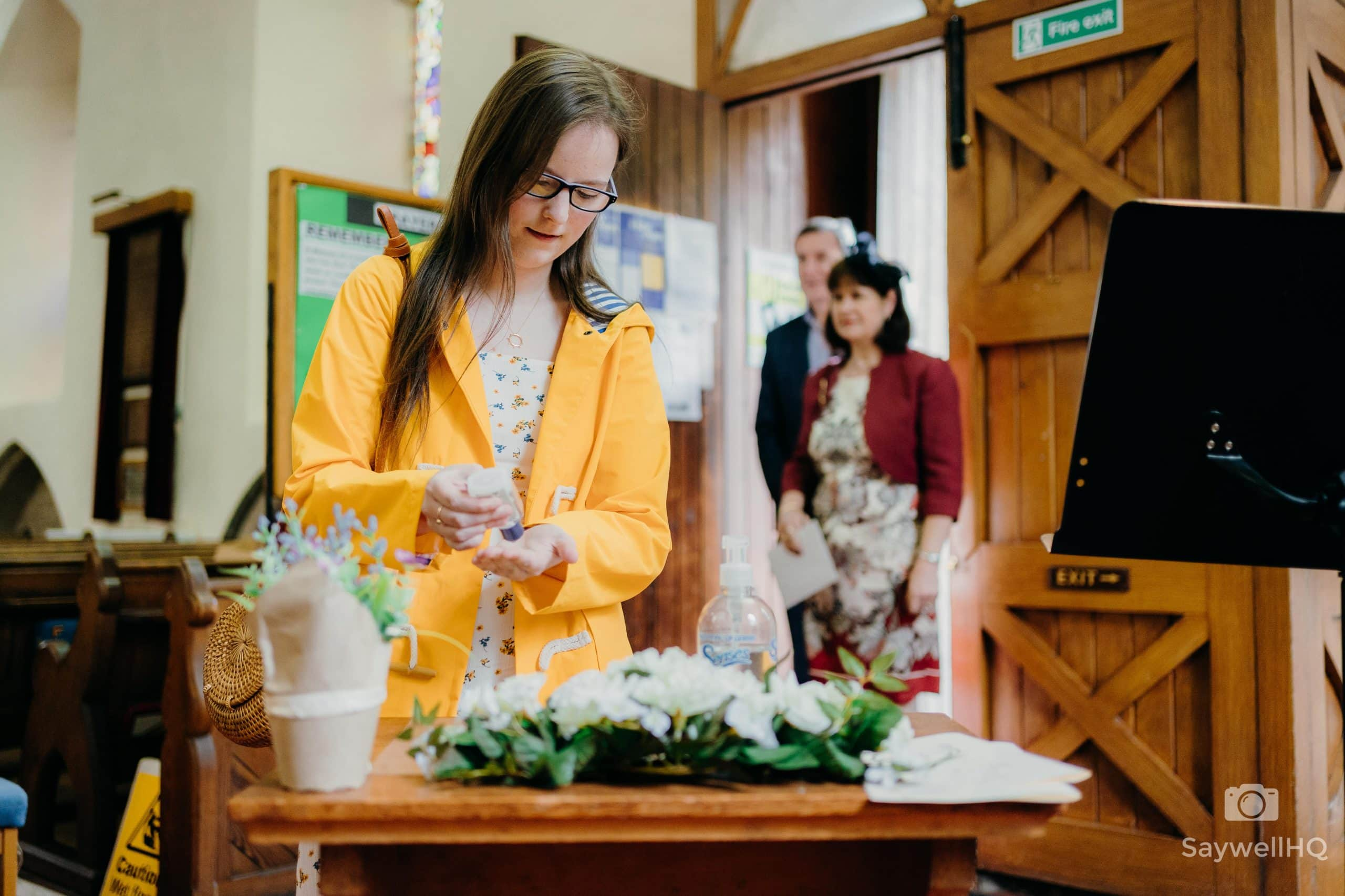 wedding guest uses hand sanitiser before entering the church for a COVID Wedding