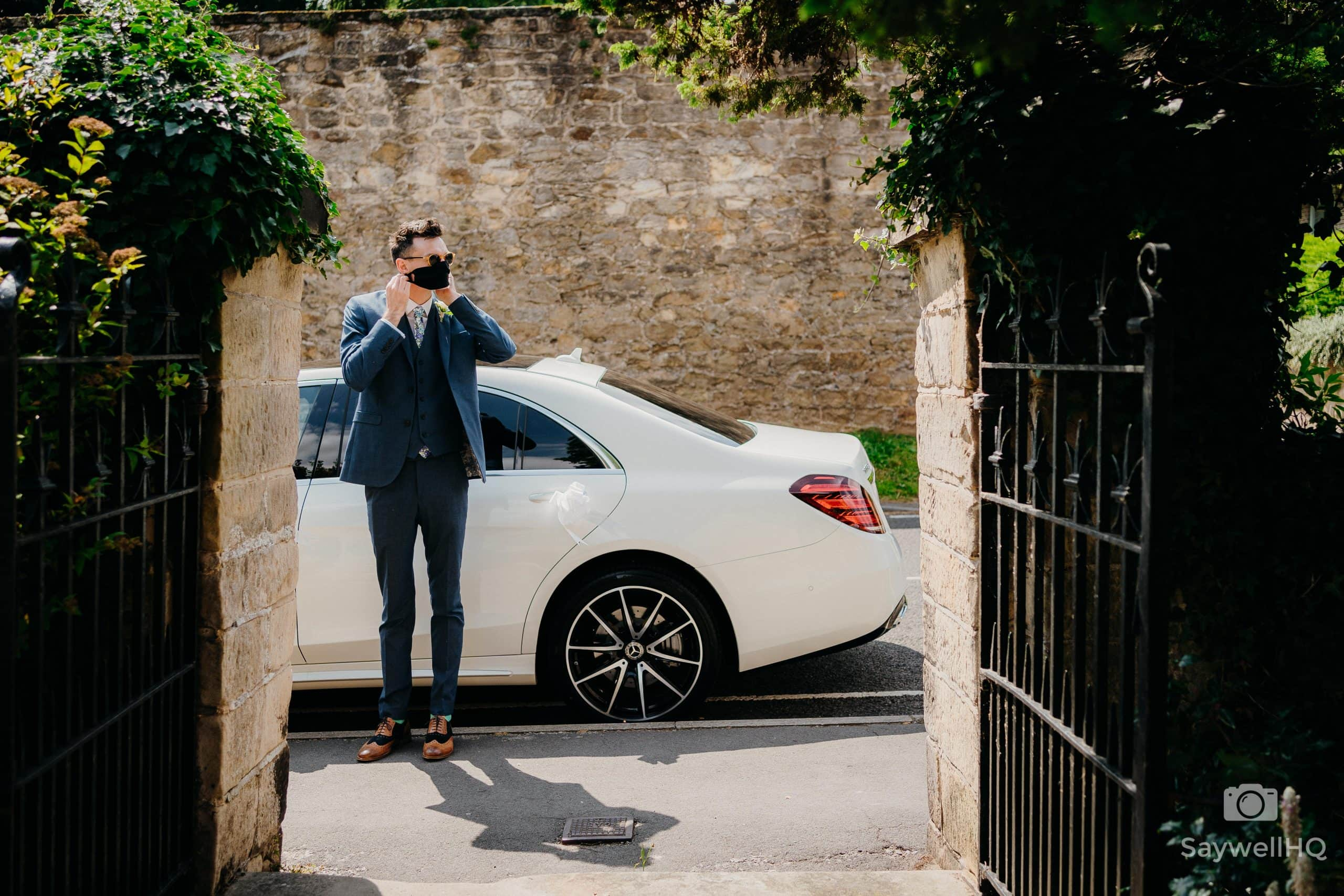 best man waiting next to the bride's car adjusting his mask at a COVID restricted wedding