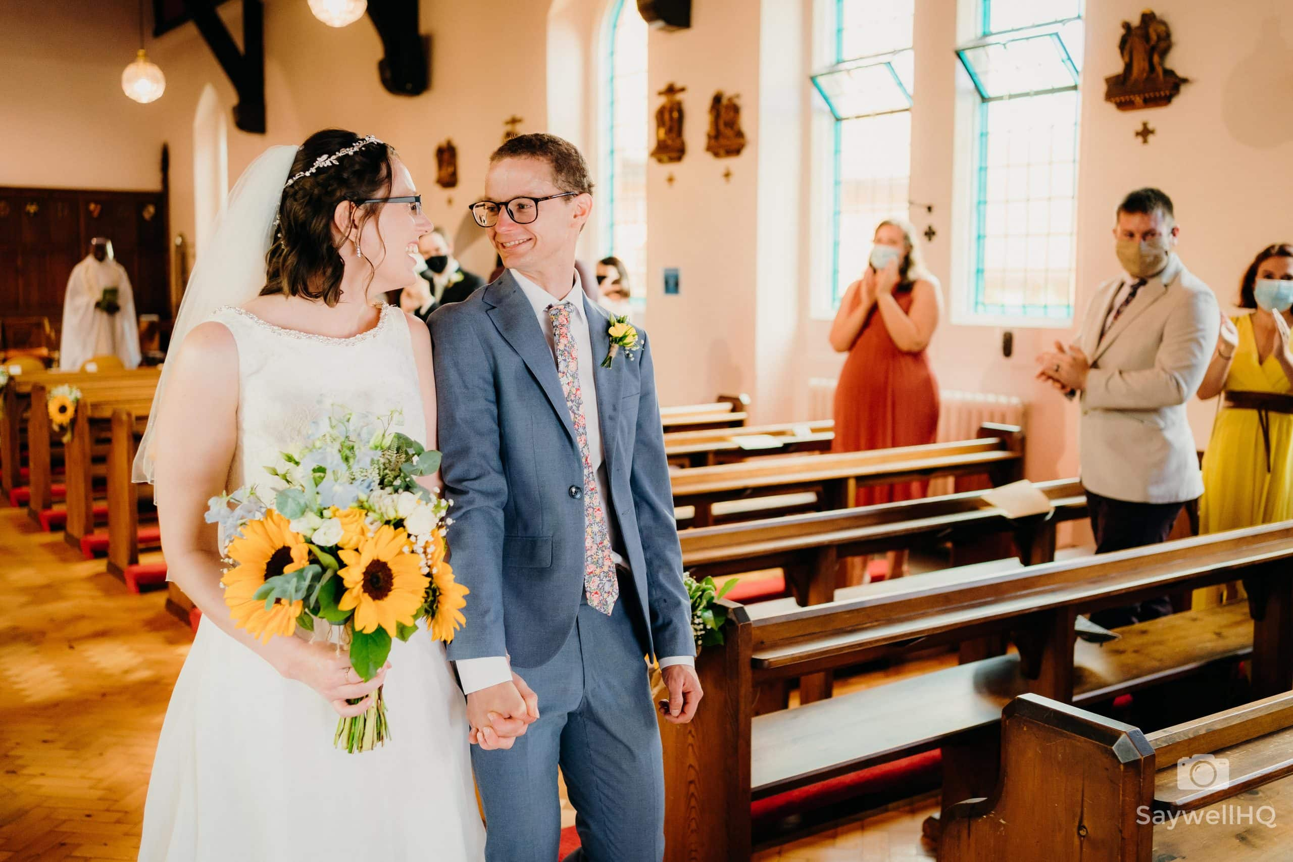 bride and groom share a loving glance at their COVID impacted wedding as they walk out of the Melbourne Derby Church