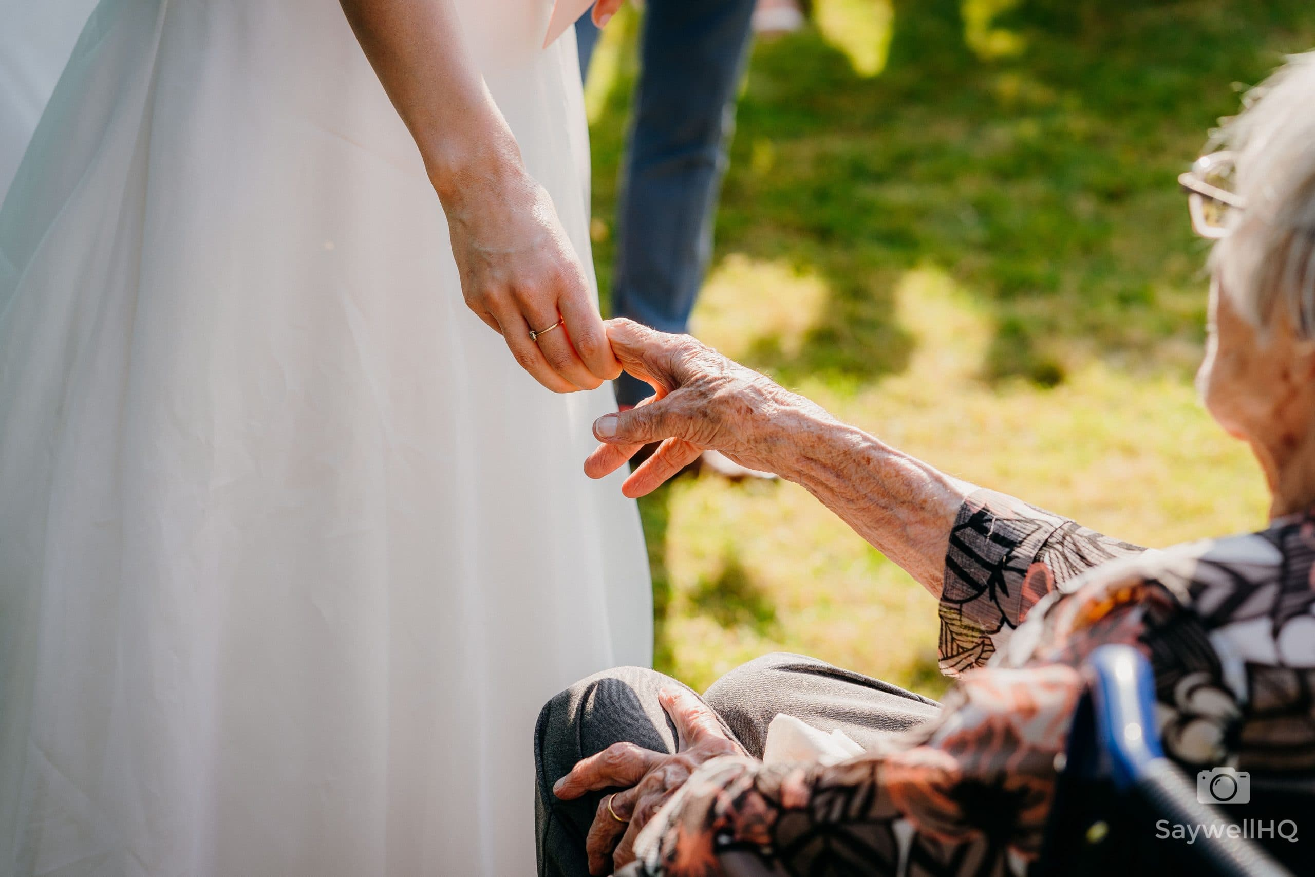 bride and grandma share a touching hand during the speeches in the garden of the Church during a covid restricted wedding