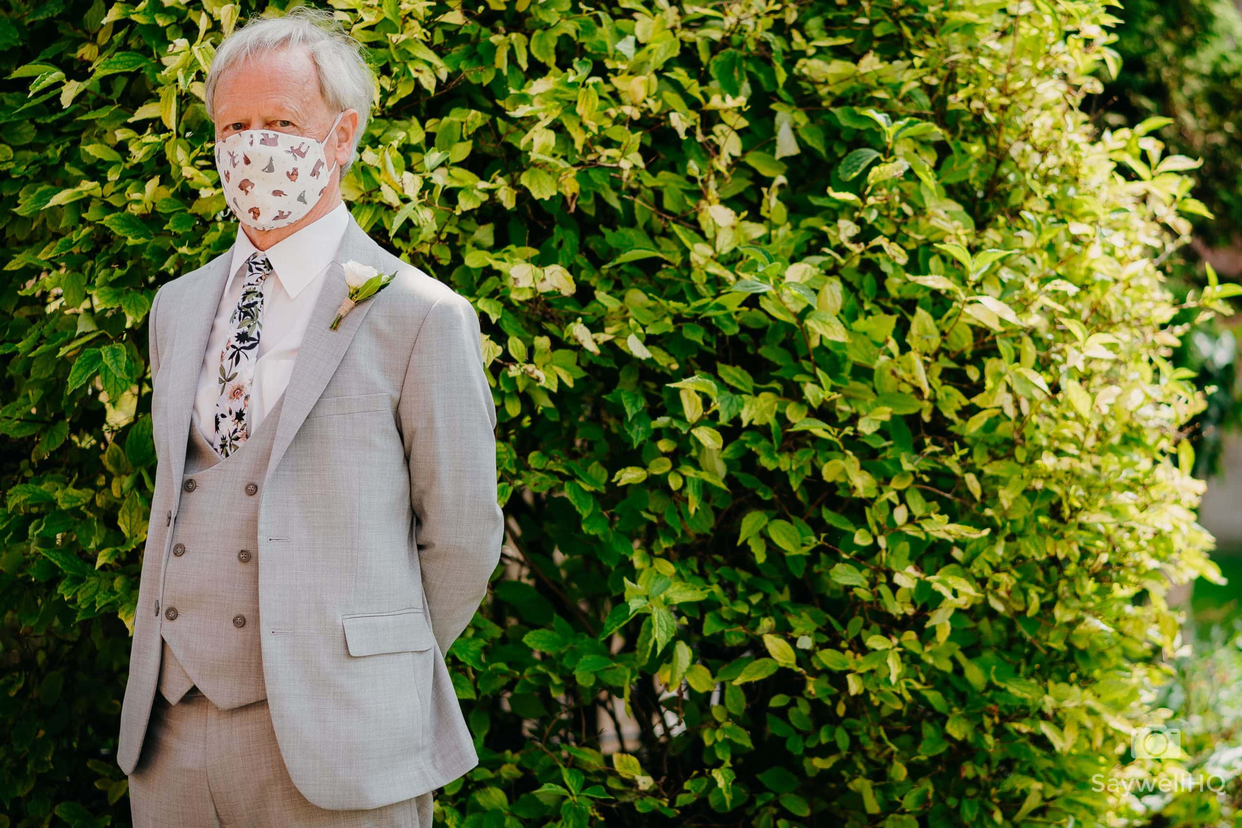 wedding guest waits outside the church wearing a mask because of the COVID restrictions in a Church