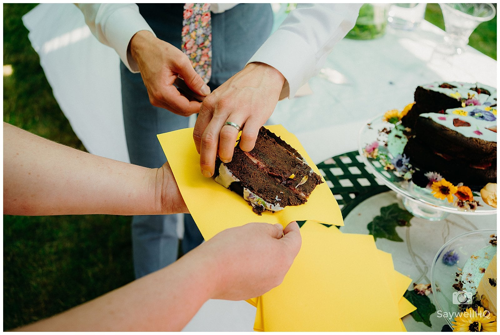 groom cuts off pieces of cake from the wedding cake and hands it to the guests