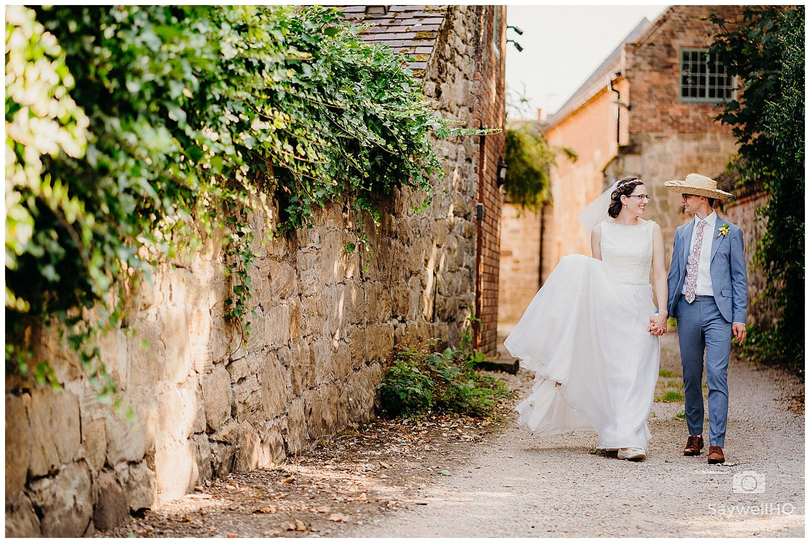 bride and groom walk hand in hand down a lovely alleyway in Melbourne Derbyshire following their derby wedding