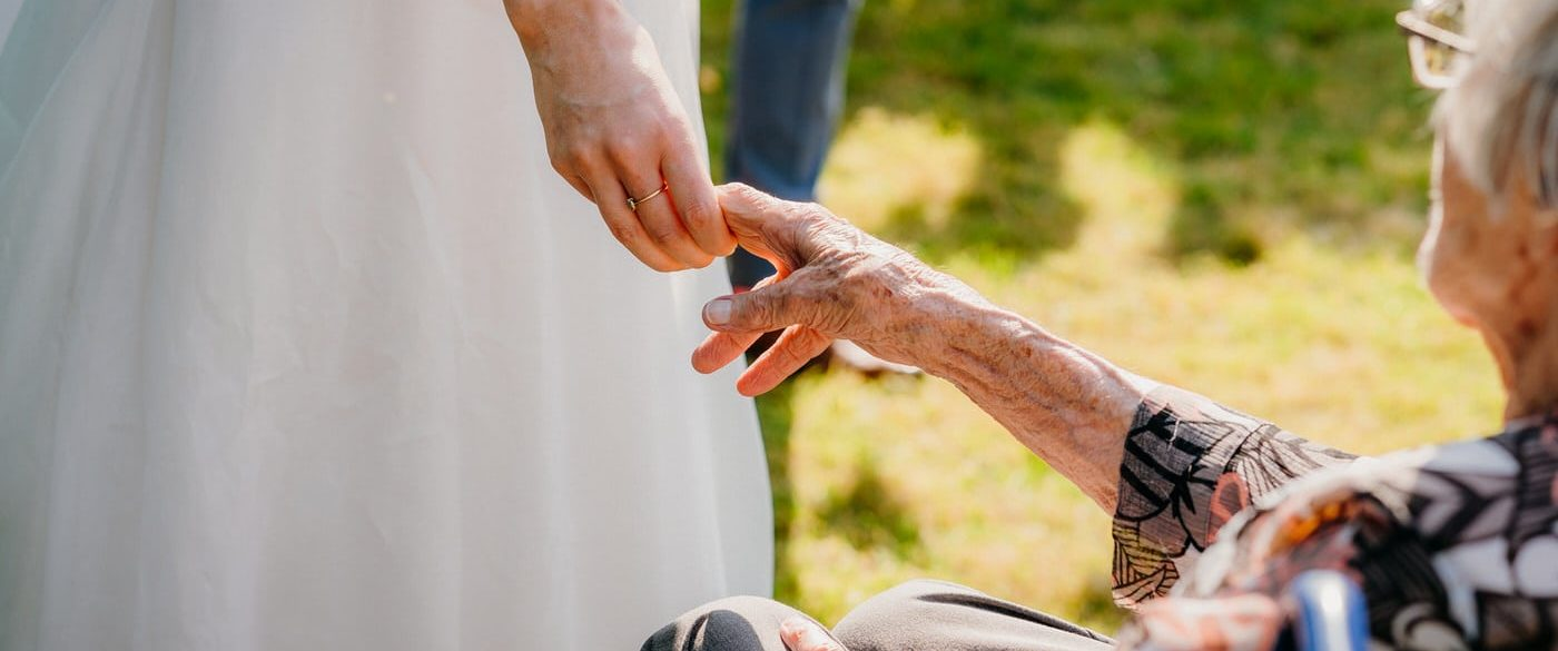bride and her grandma holding hands on her grand daughters wedding day