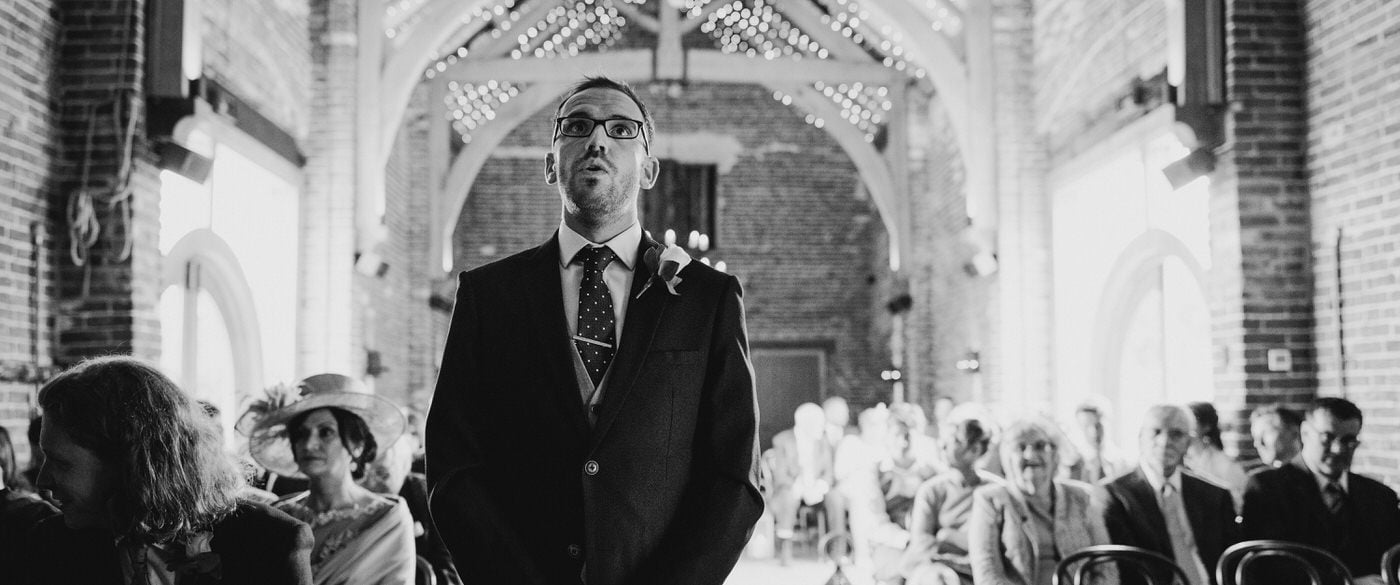 groom looking nervous at a barn wedding with large beams and lights