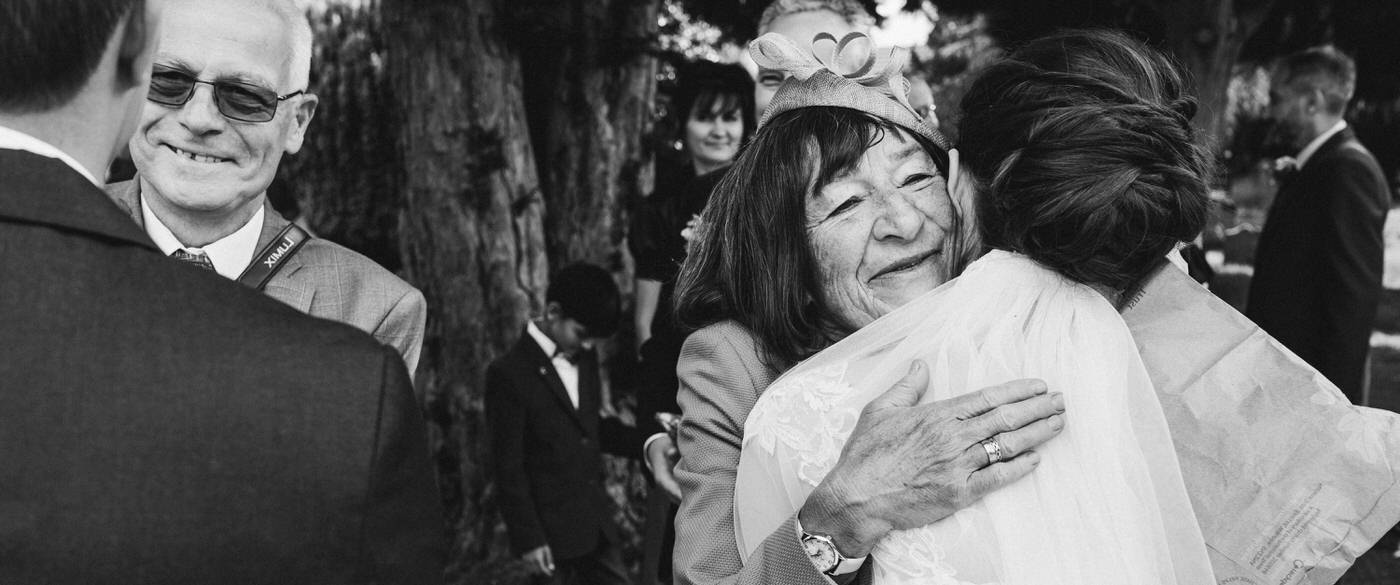 grandparents hugging the bride and the wedding day in the grounds of the church