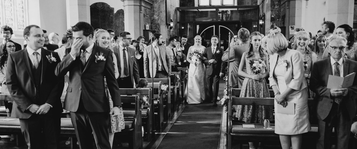 groom getting emotional as his bride walks down the aisle with her dad
