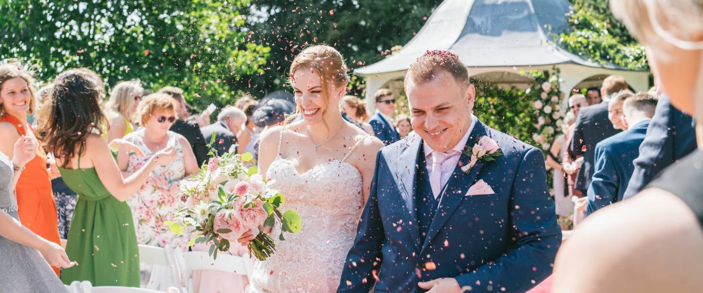 bride and groom getting covered in confetti after their outdoor wedding