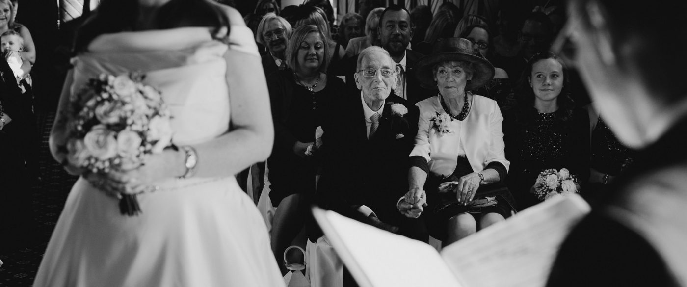 brides elderly parents looking on during their daughters wedding ceremony