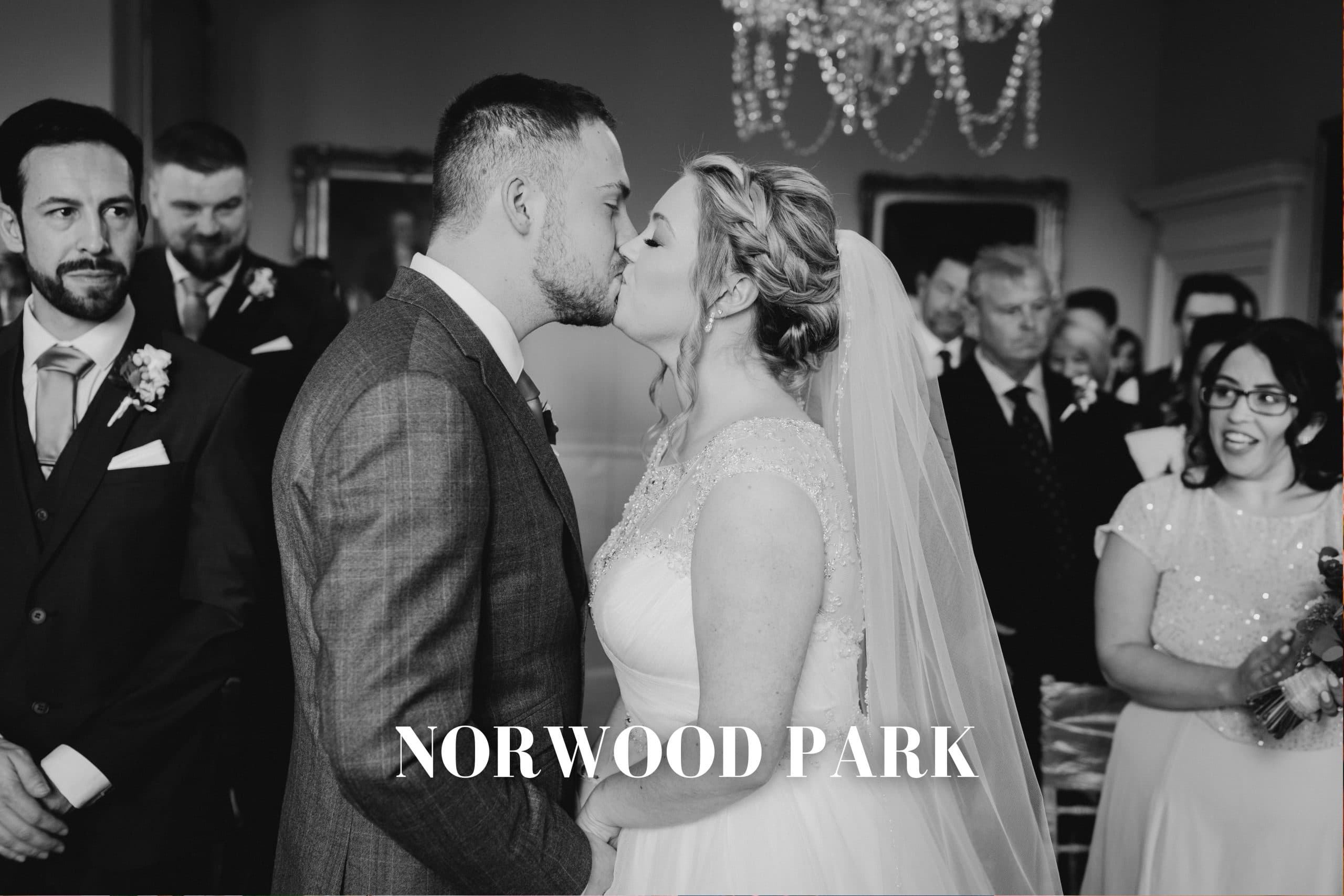 bride and groom kiss during their wedding ceremony at Norwood park