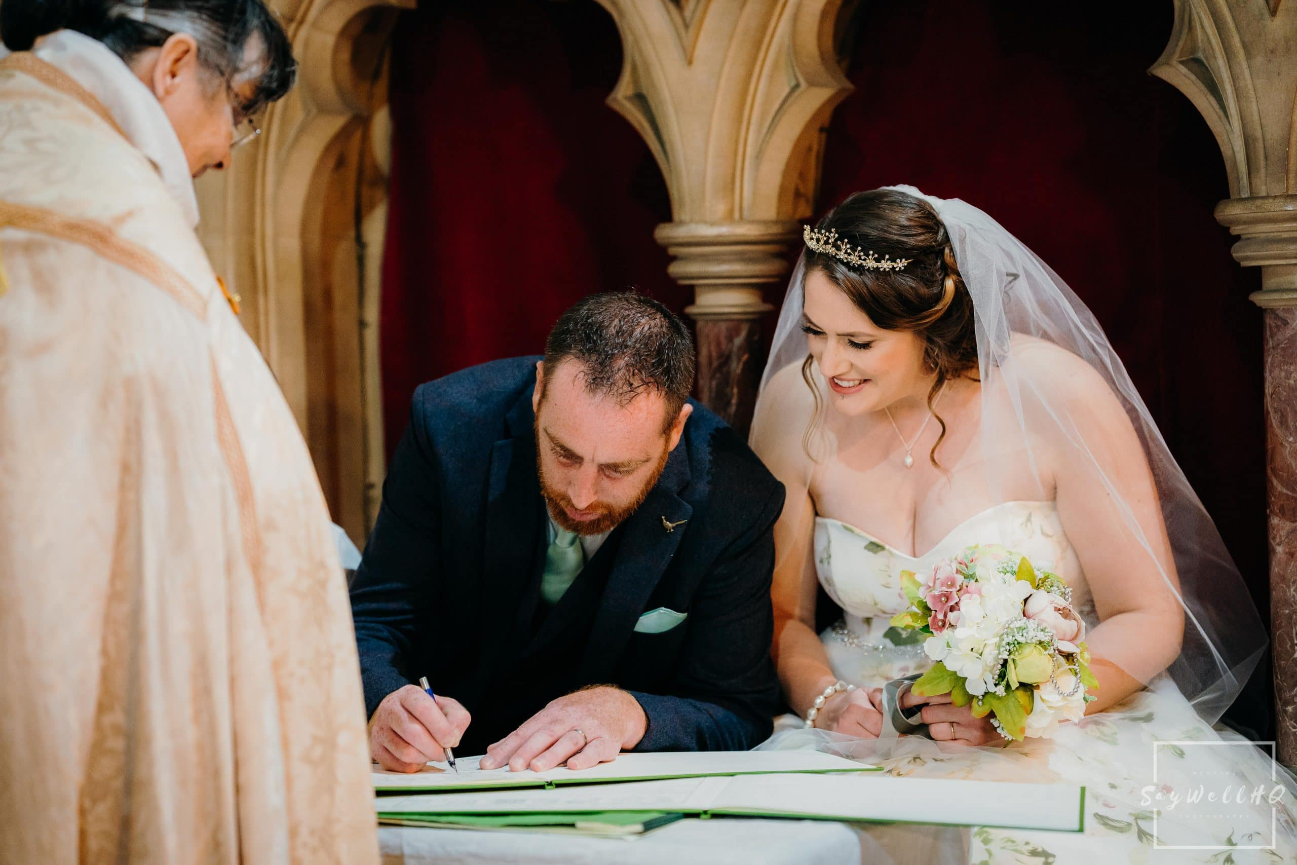 Lincoln wedding photographer - bride and groom sign the wedding register after their Lincoln Church wedding
