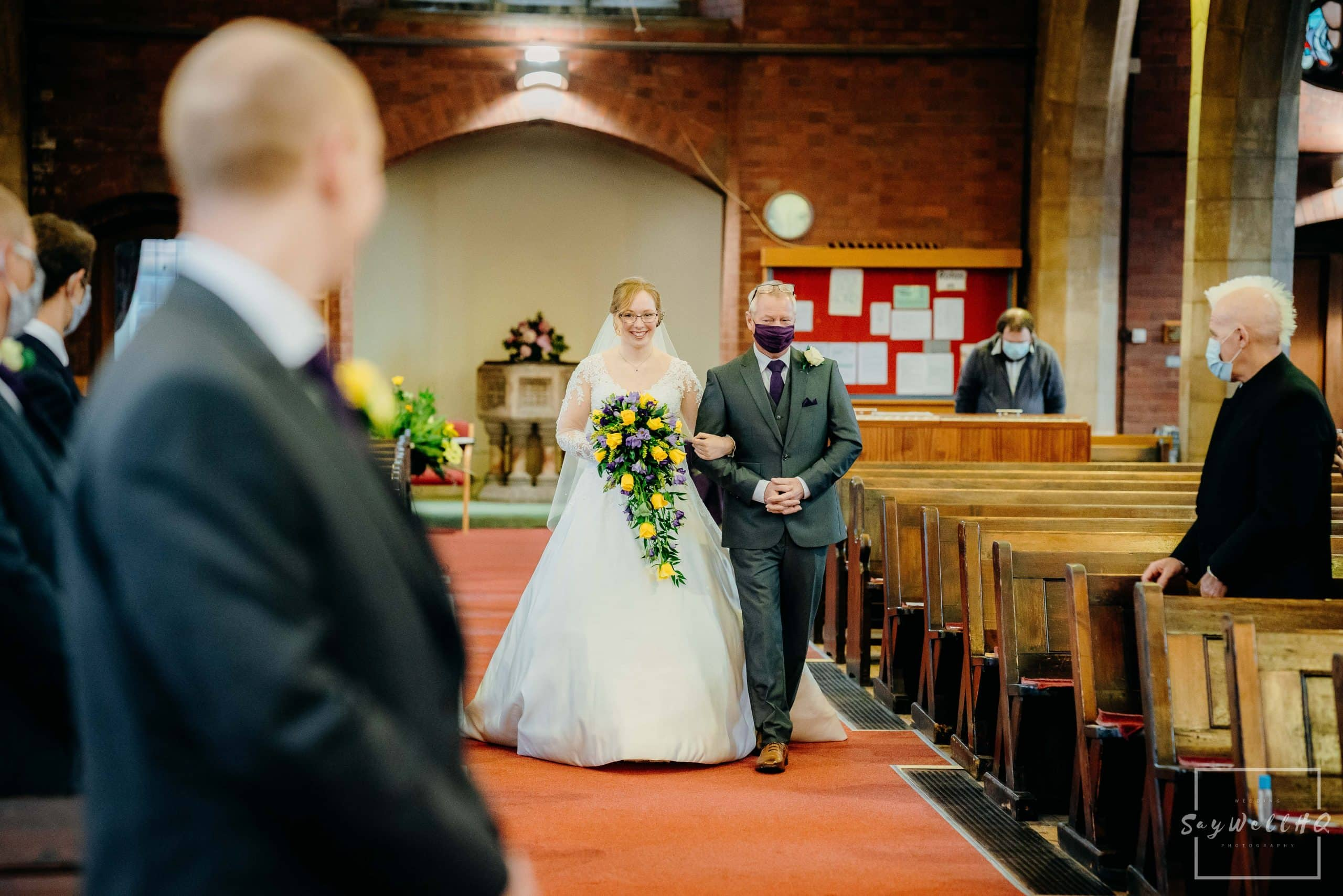 Bride and her father walking down the aisle at her micro wedding at St Judes Church in Mapperley Nottingham