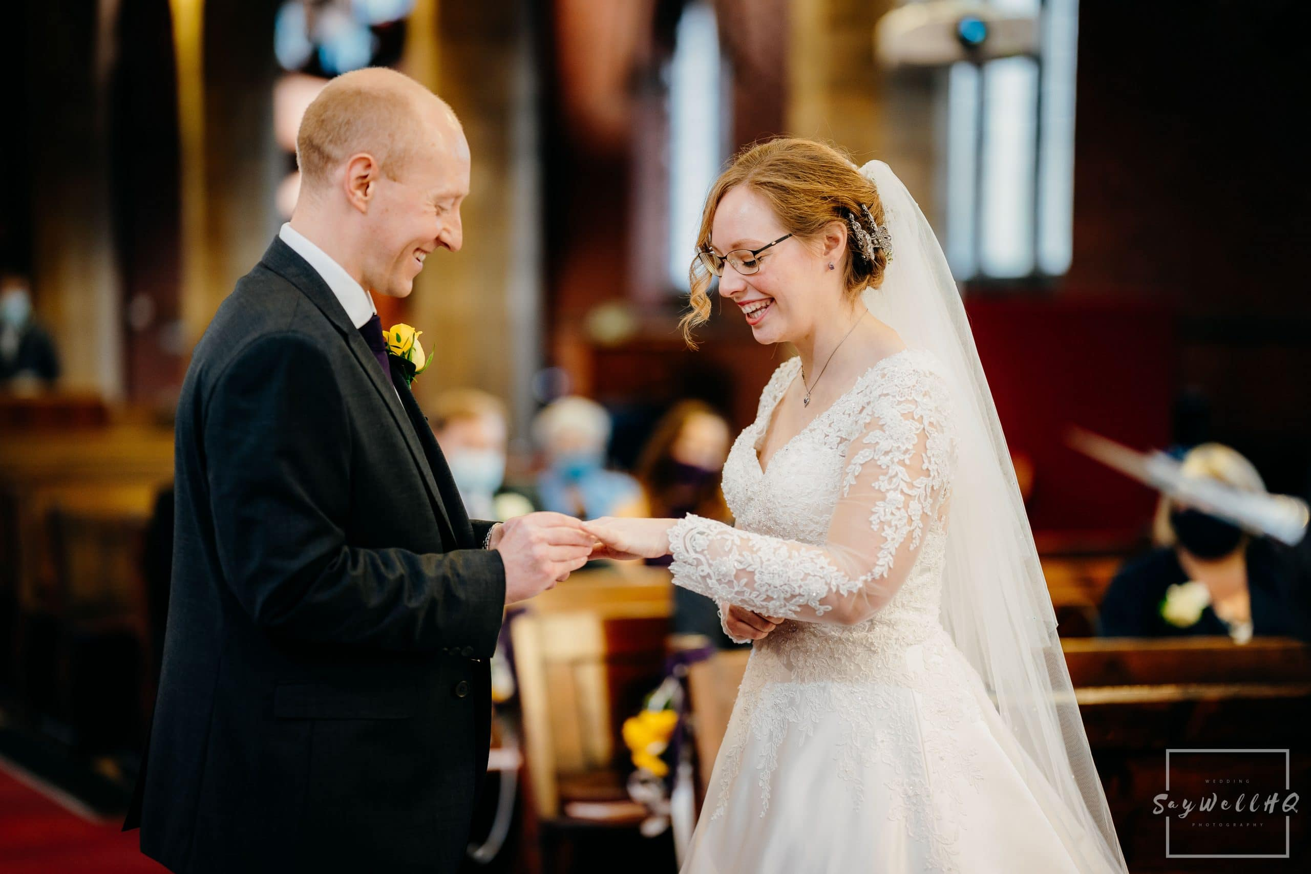 Bride and groom exchange rings at their micro wedding at St Judes Church in Mapperley Nottingham