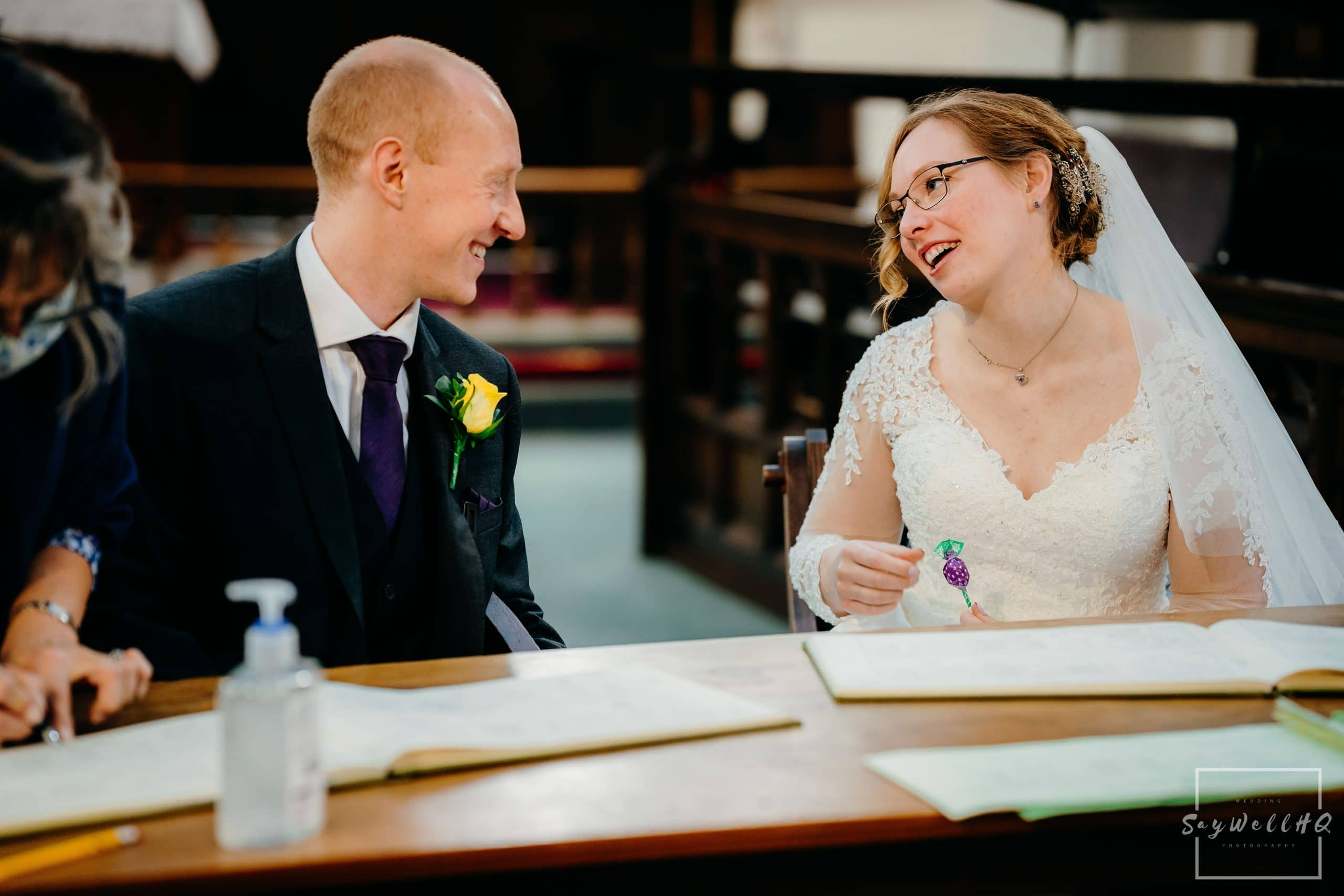 Bride and groom chat away during the signing of the register at their micro wedding at St Judes Church in Mapperley Nottingham