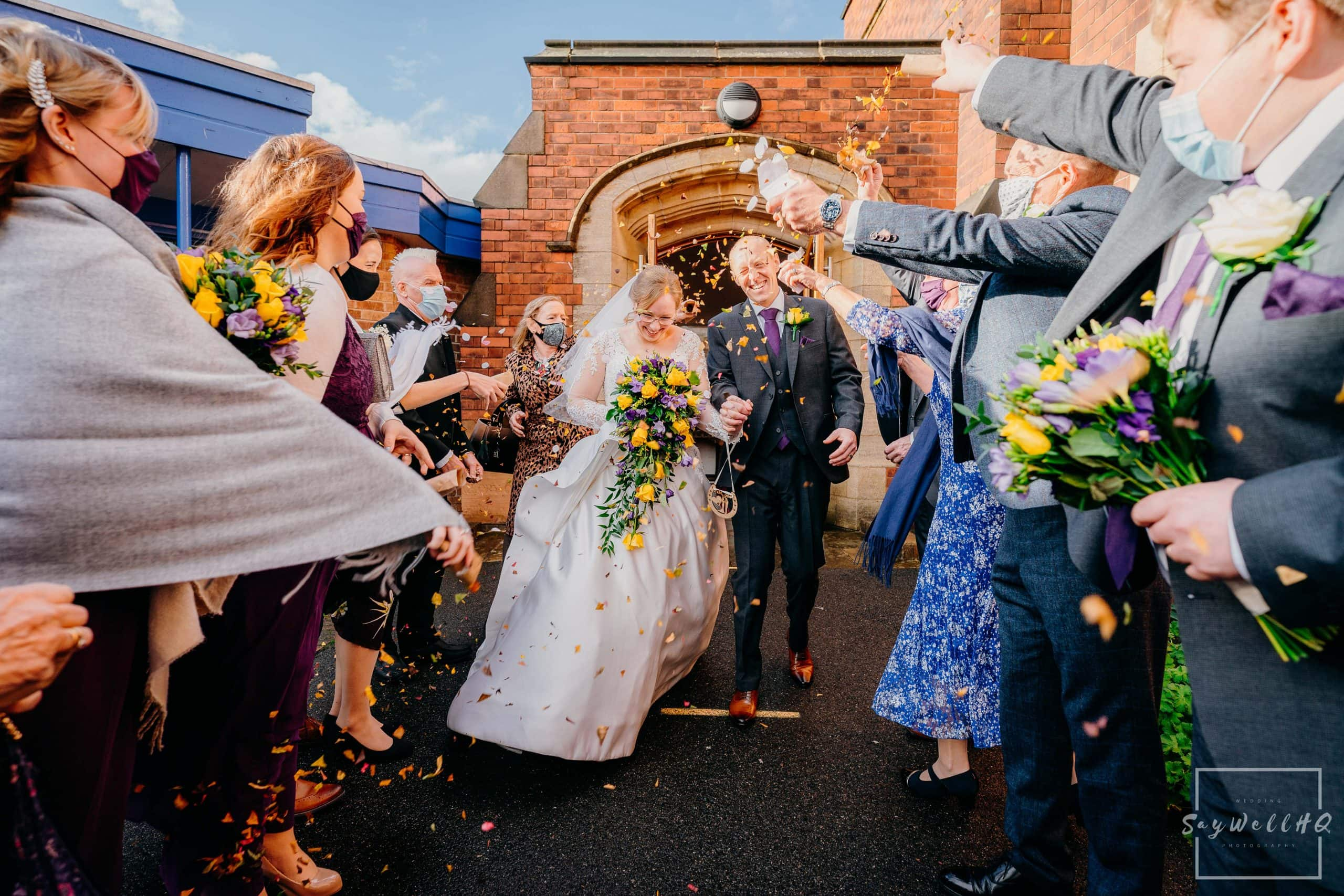Bride and Groom get covered in Confetti after their micro wedding at St Judes Church in Mapperley Nottingham