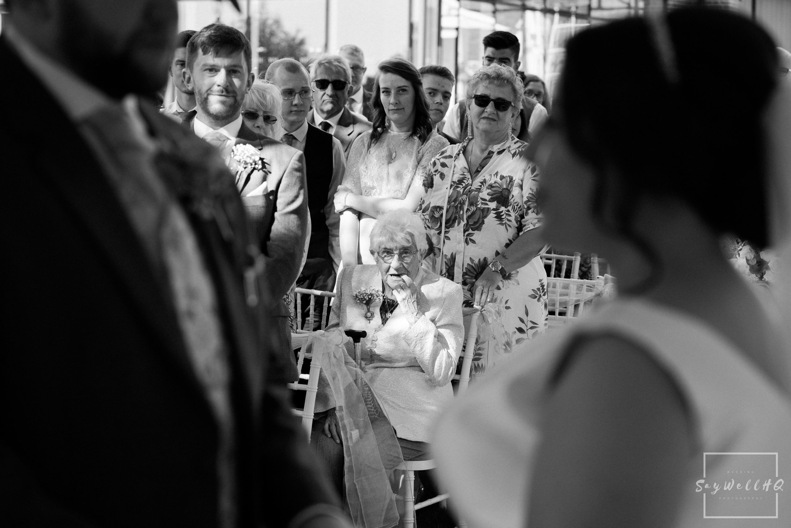 Derby Wedding Photographer - grandma looking at the bride and groom during the wedding ceremony in derby.