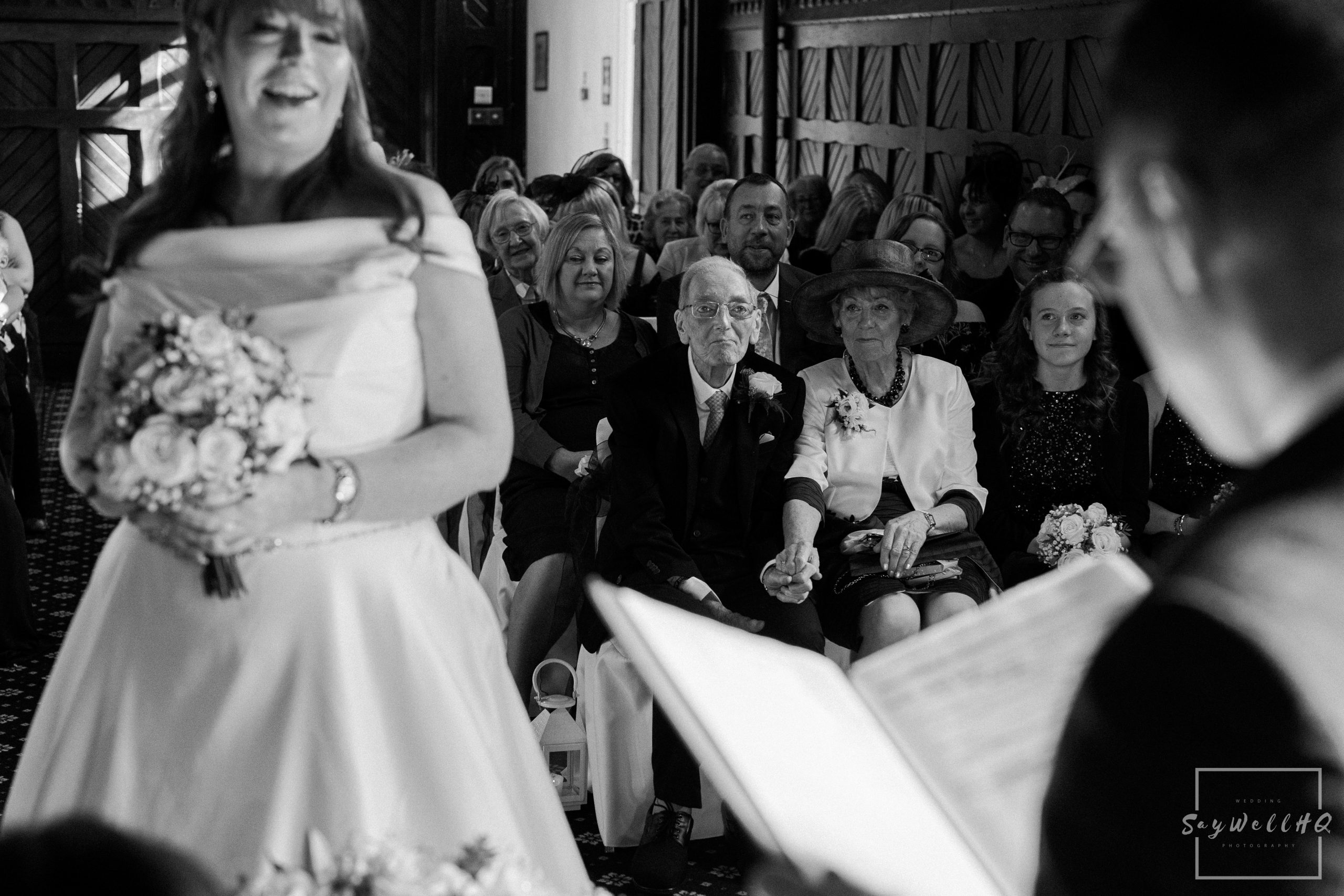 Derby Wedding Photographer - brides parents holding hands during their daughters wedding ceremony