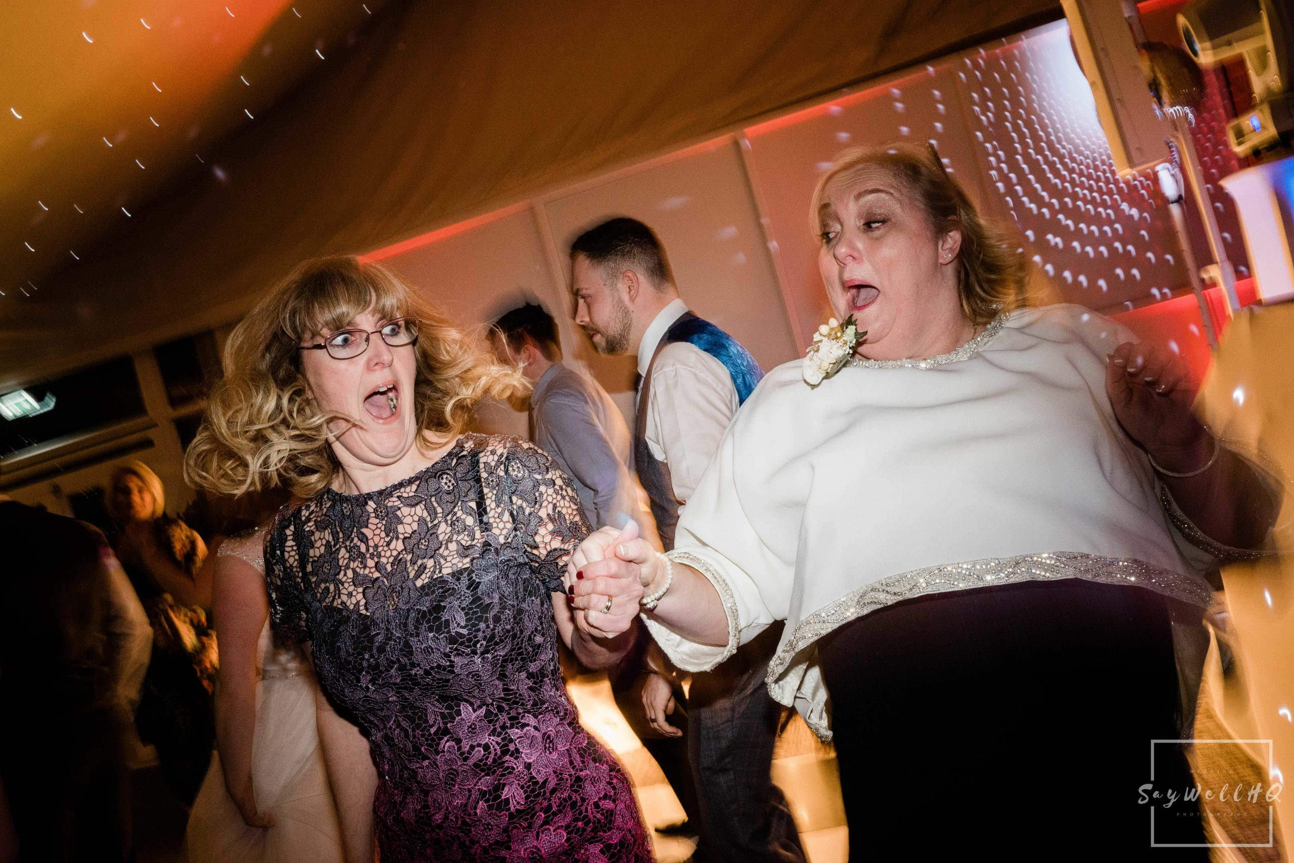 Derby Wedding Photographer - mother of the bride and her best friend enjoying the disco music at the end of the wedding day