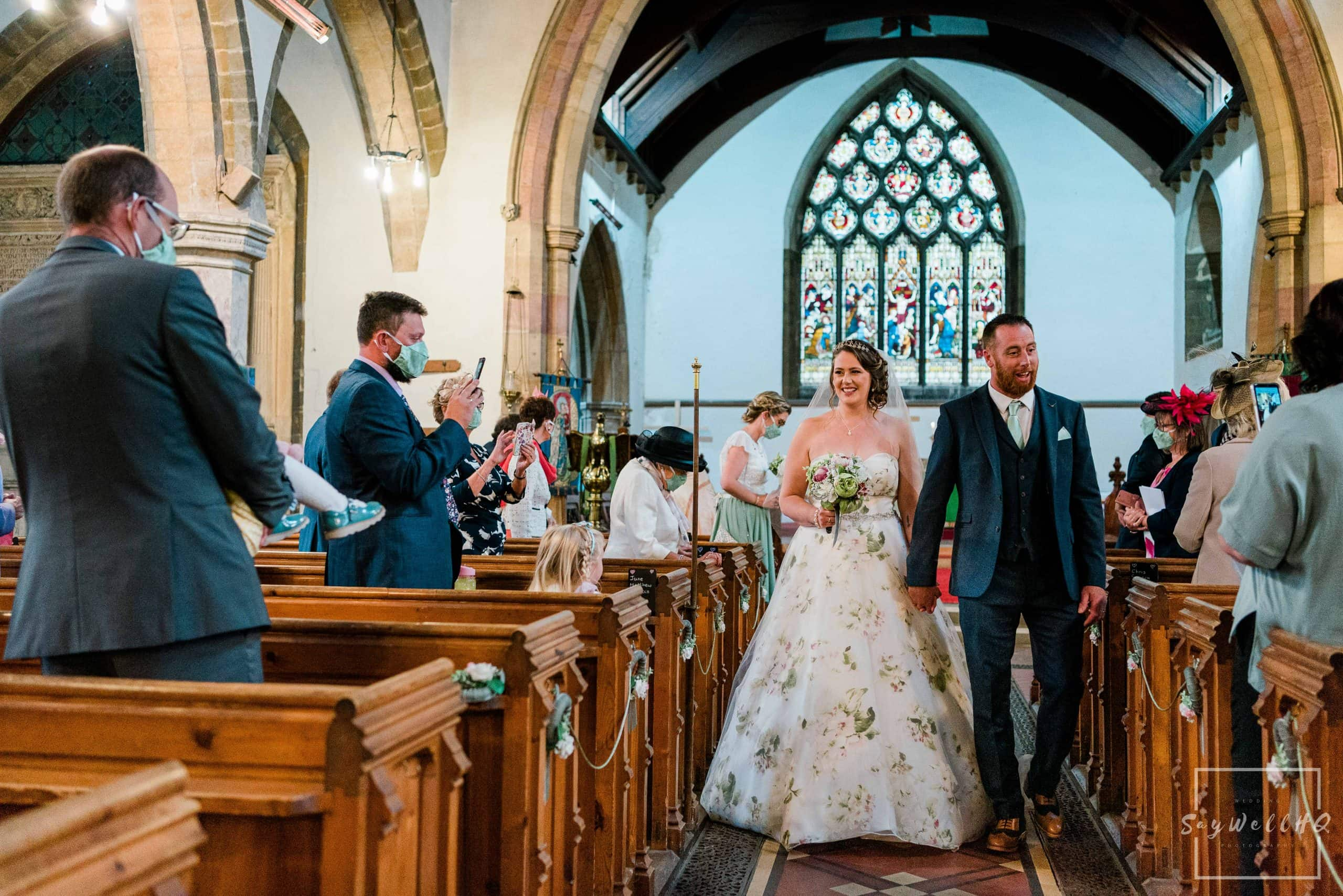 Covid Wedding Photography - bride and groom walking down the aisle following their covid 19 restricted wedding - wedding photography by Andy Saywell of SaywellHQ