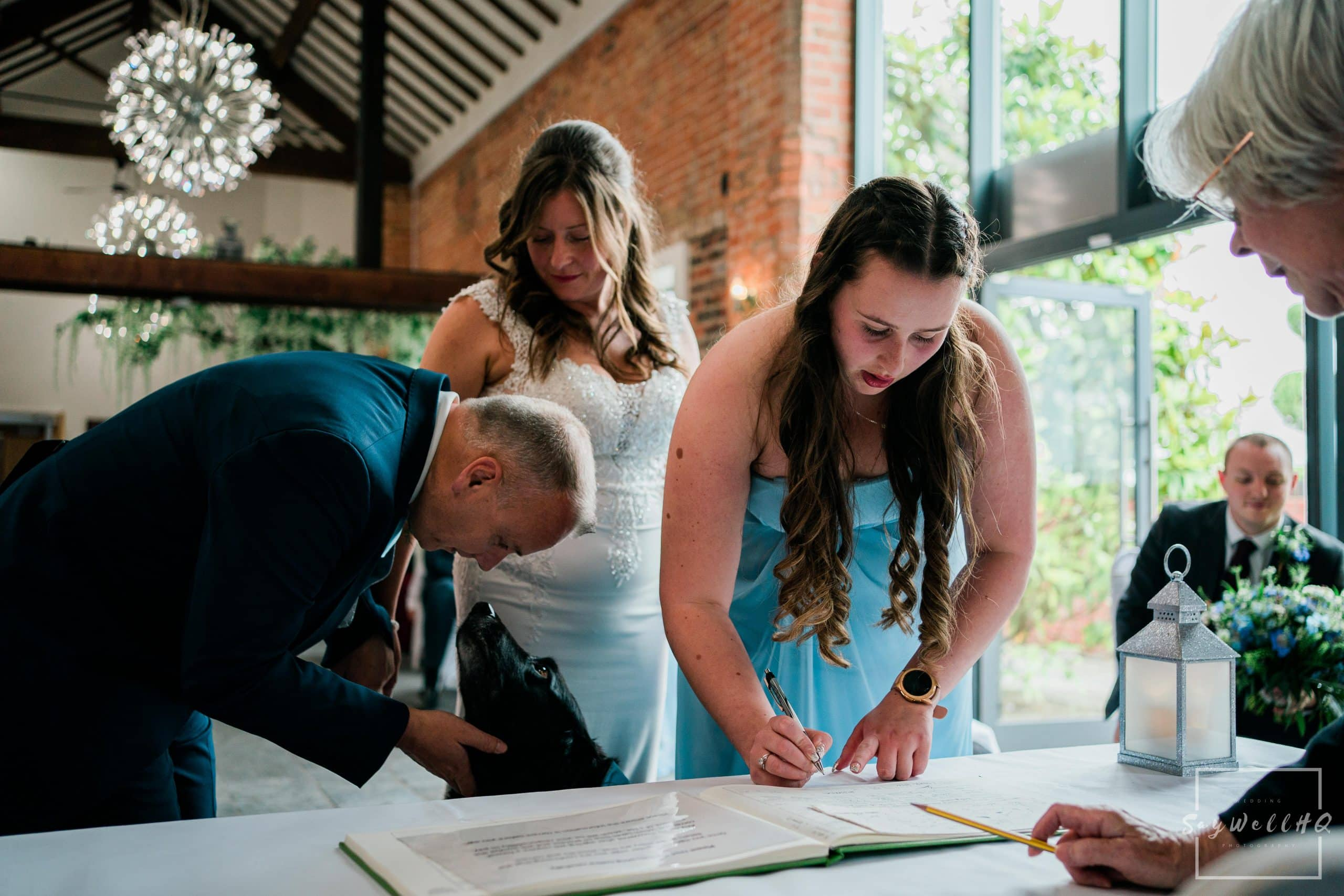 signing the register whilst a pet dog looks on at a Goosedale wedding - Wedding Photography by goosedale wedding photographer Andy Saywell of SaywellHQ